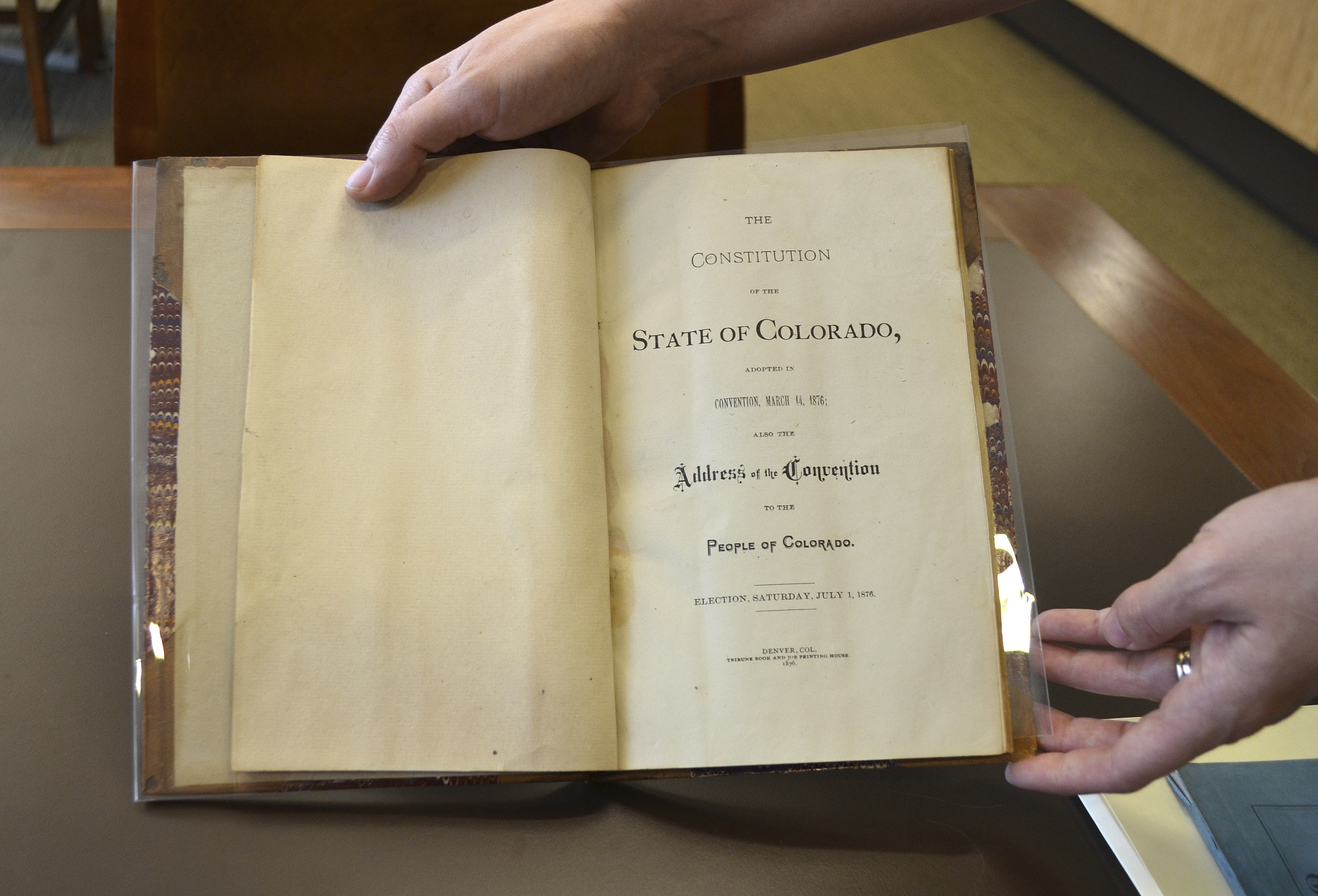 <p>Reference librarian Sarah Gilmor holds an 1876 copy of the Colorado Constitution at the Stephen H. Hart Library & Research Center in Denver.</p>