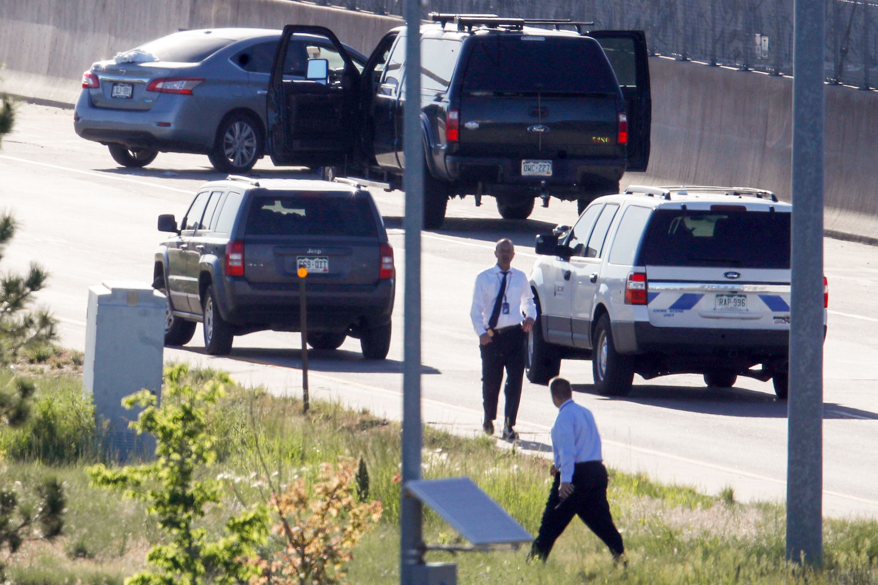 Denver Police Department detectives, foreground, investigate near where a Nissan sedan, top left, being driven by an Uber driver crashed into a retaining wall along Interstate 25 south of downtown Denver early Friday, June 1, 2018.