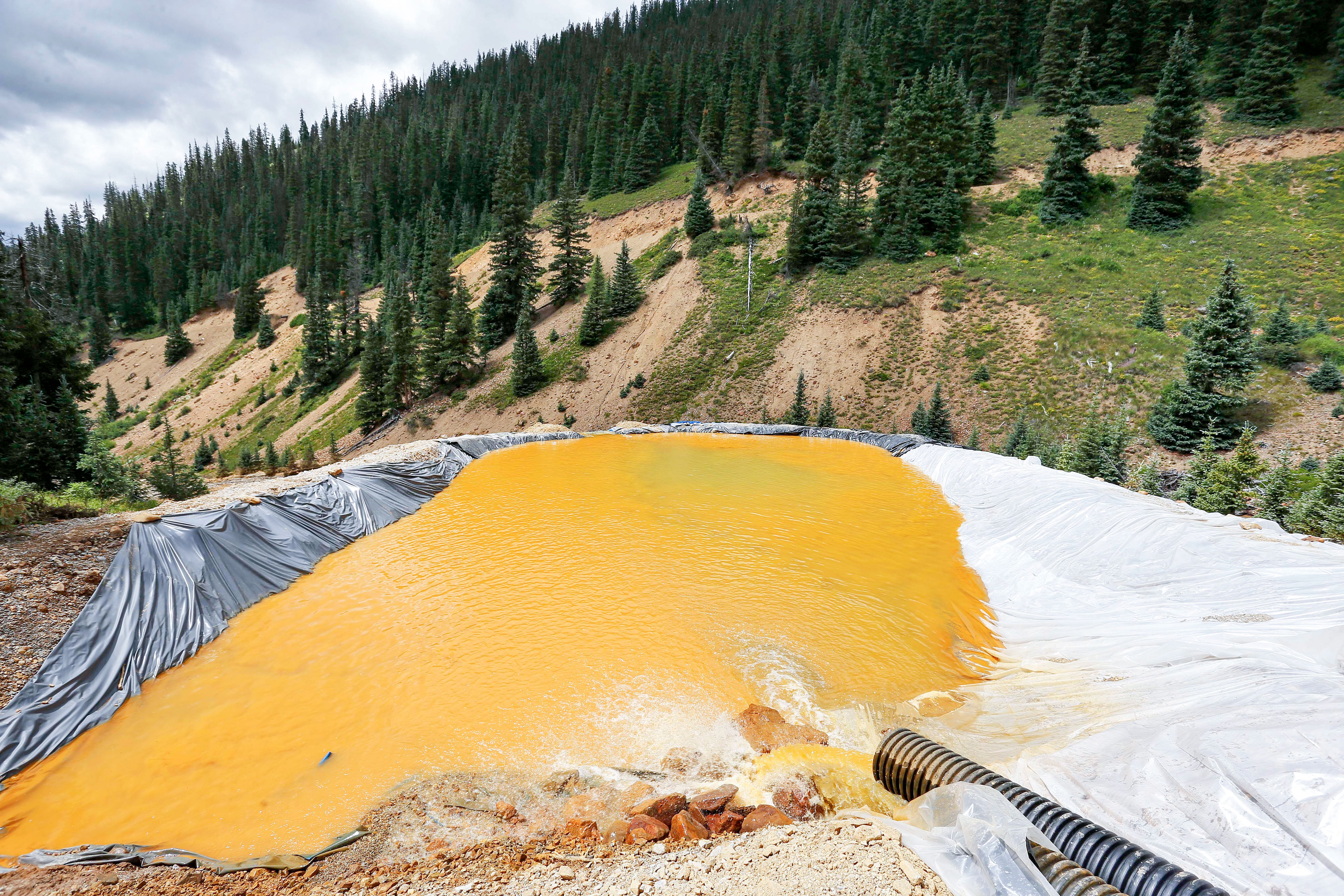 <p>Wastewater flows through a retention pond built to contain and remove heavy metals from the Gold King Mine outside Silverton, Colo., Aug. 12, 2015</p>