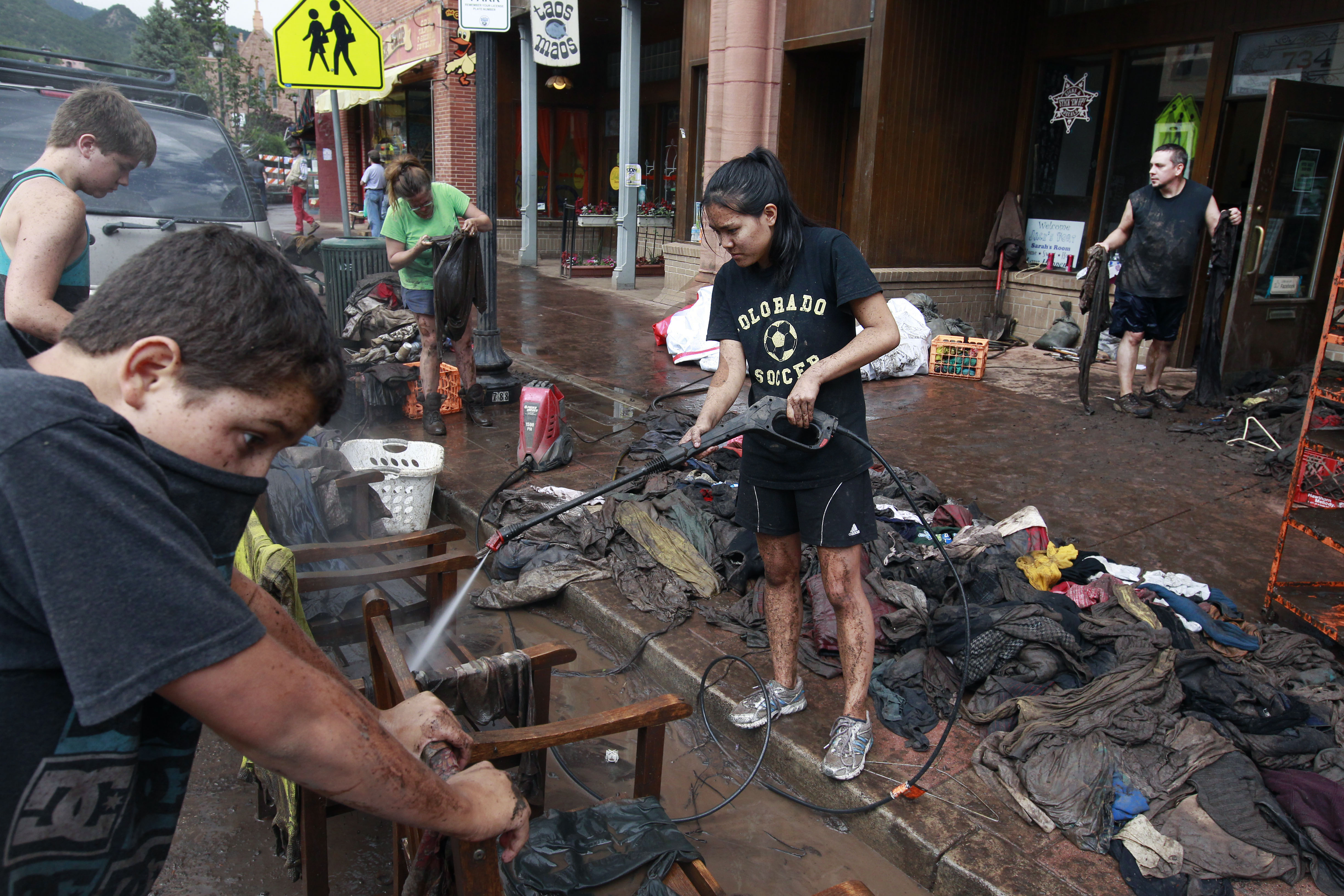 <p>Volunteer and recent local high school graduate Alex Caffery, center, helps local merchant Angie Findley, third from left, wash mud off merchandise at her Stick Em Up! store, which was heavily damaged a few days earlier in a flash flood, in Manitou Springs, Colo., Monday Aug. 12, 2013.</p>