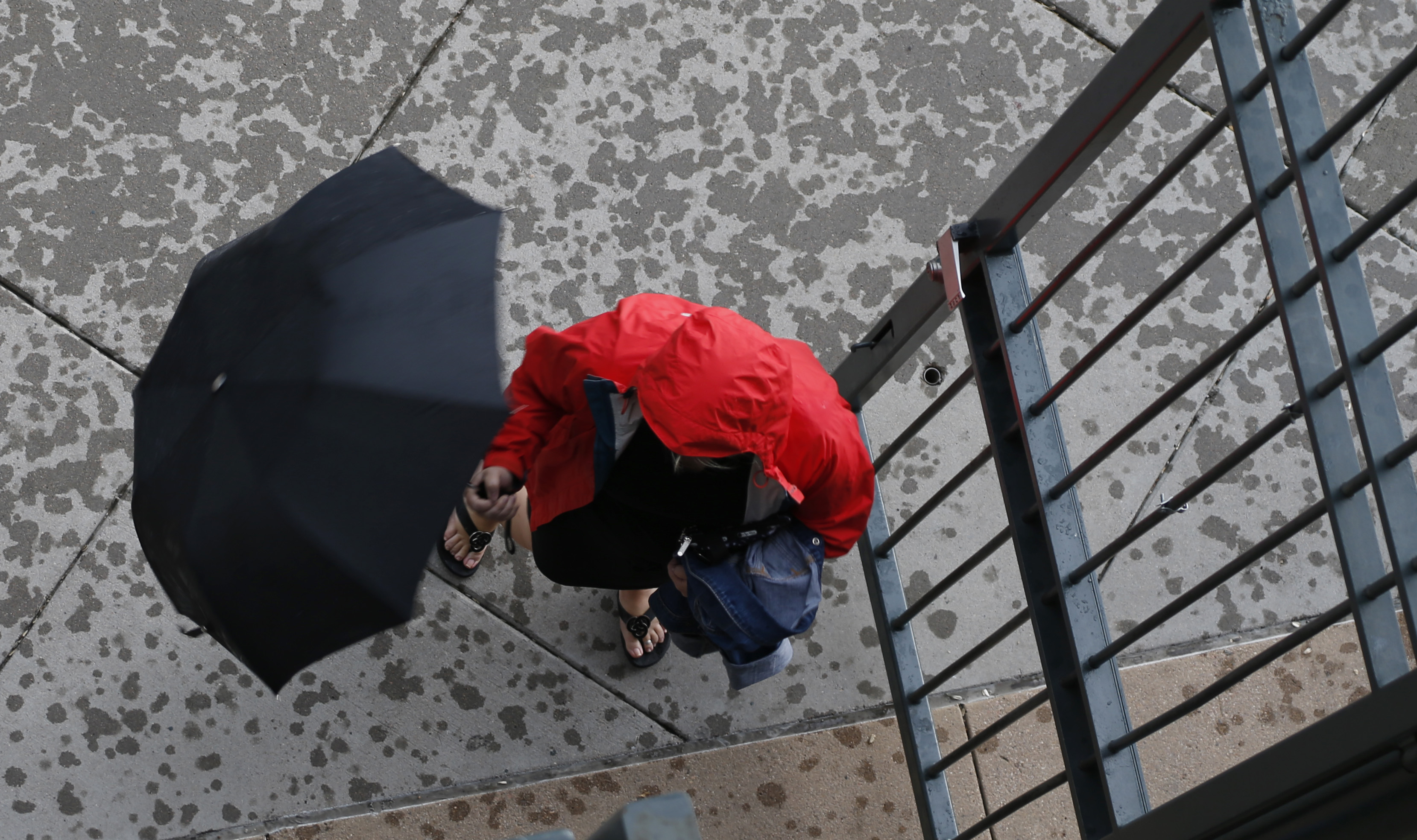 An unidentified pedestrian pulls down an umbrella to enter a building as rain falls from a storm sweeping over downtown Denver late Wednesday, June 3, 2015.