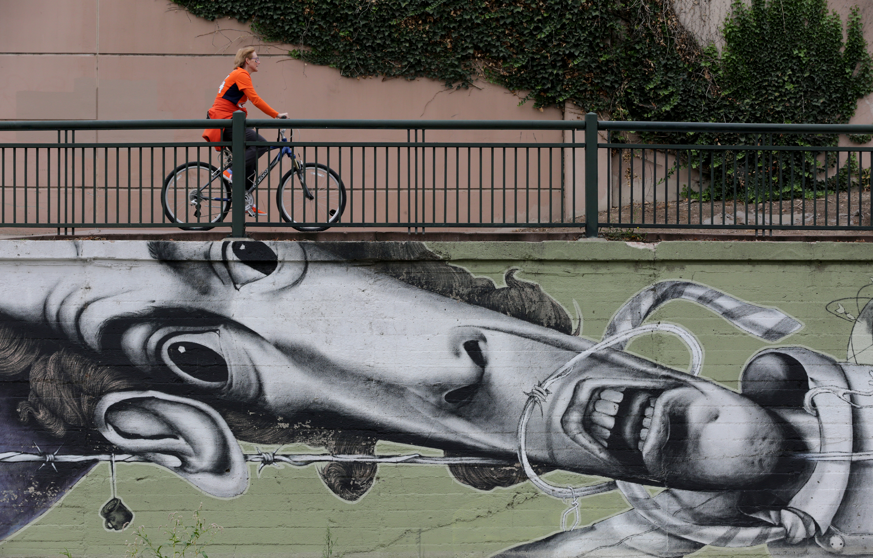 <p>A cyclist rideson the Cherry Creek bike path above a graffiti mural commissioned by the city of Denver near Confluence Park on Sunday, Oct. 4, 2015.</p>