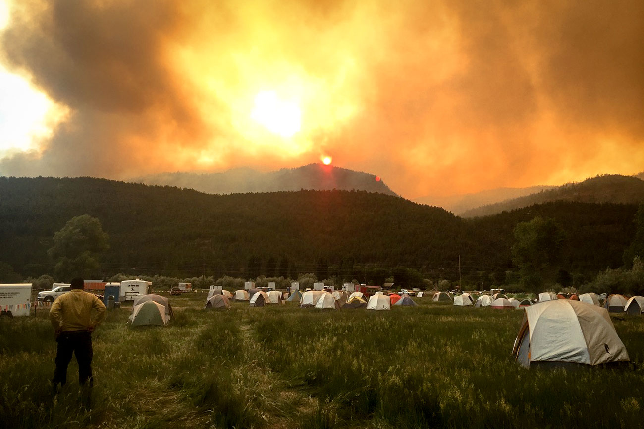 <p>A firefighter looks on from the 416 Fire base camp outside Durango, Colo., June 12, 2018.</p>
