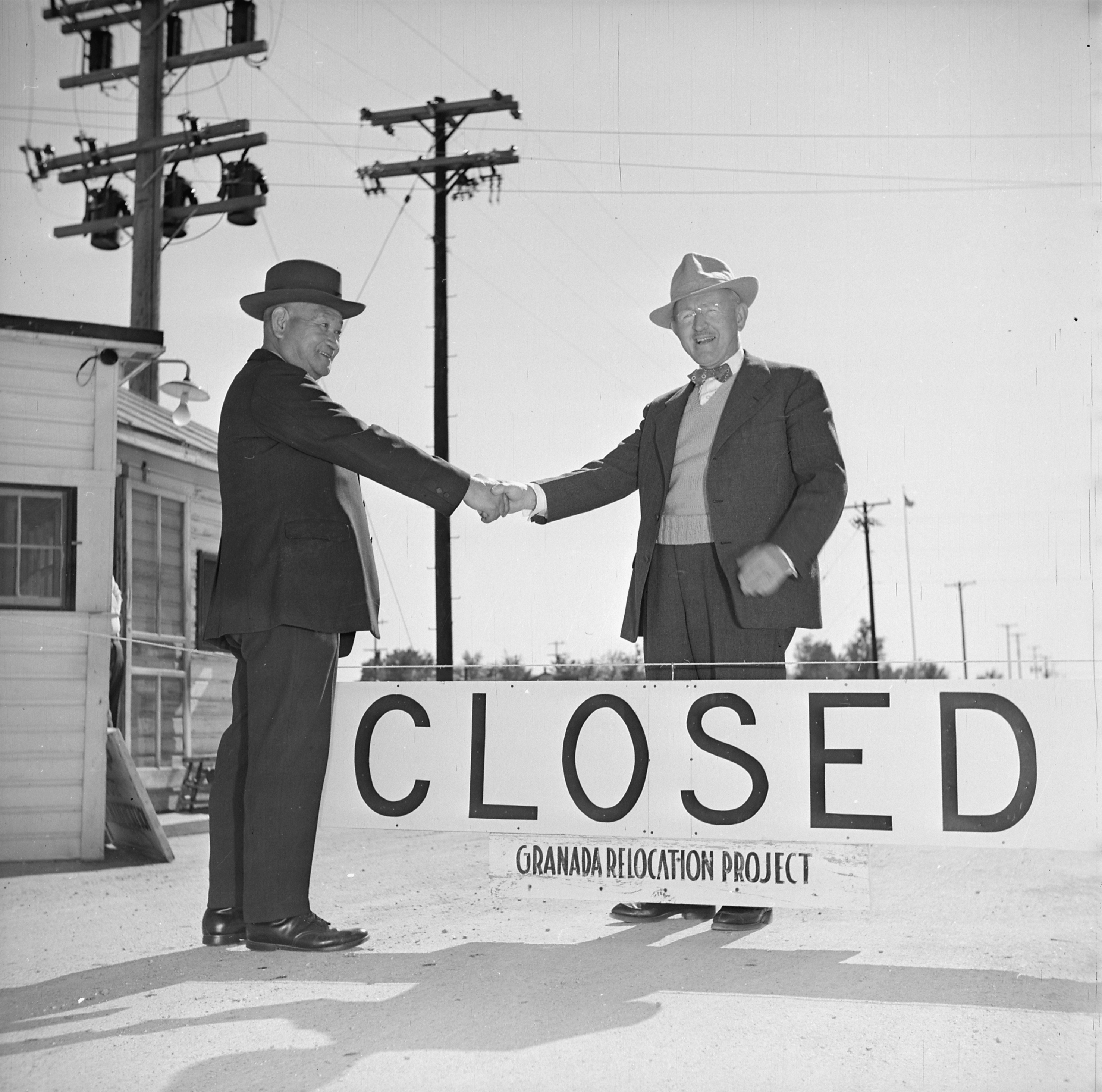 """<p>A public domain photo taken by the Department of the Interior. The original caption reads:Shuichi Yamamoto, last Amache evacuee to leave the Granada Project Relocation Center, says """"Goodbye"""" to Project Director James G. Lindley, as War Relocation Authority camp is officially closed October 15, 1945. Mr. Yamamoto, 65 years of age, is returning to his former home in Marysville, California.</p>"""