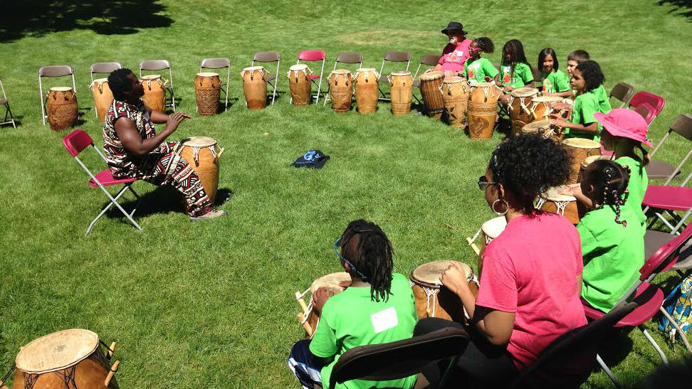 <p>Adopted children perform in a drum circle at the African and Caribbean Heritage Camp.</p>