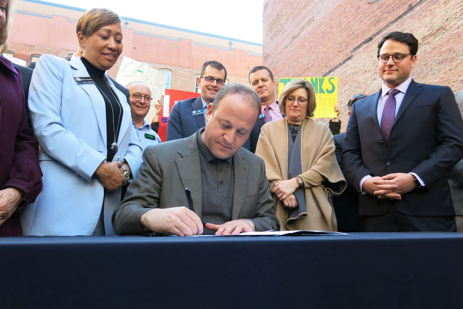 <p>Gov. Jared Polis signs his first environmental executive order on Thursday, Jan. 17, 2019, to put more electric cars and buses on the road. He's flanked by state representatives and leaders of environmental groups.</p>