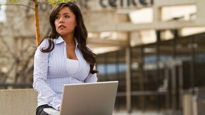 <p>A Native American young woman on campus with a laptop.</p>