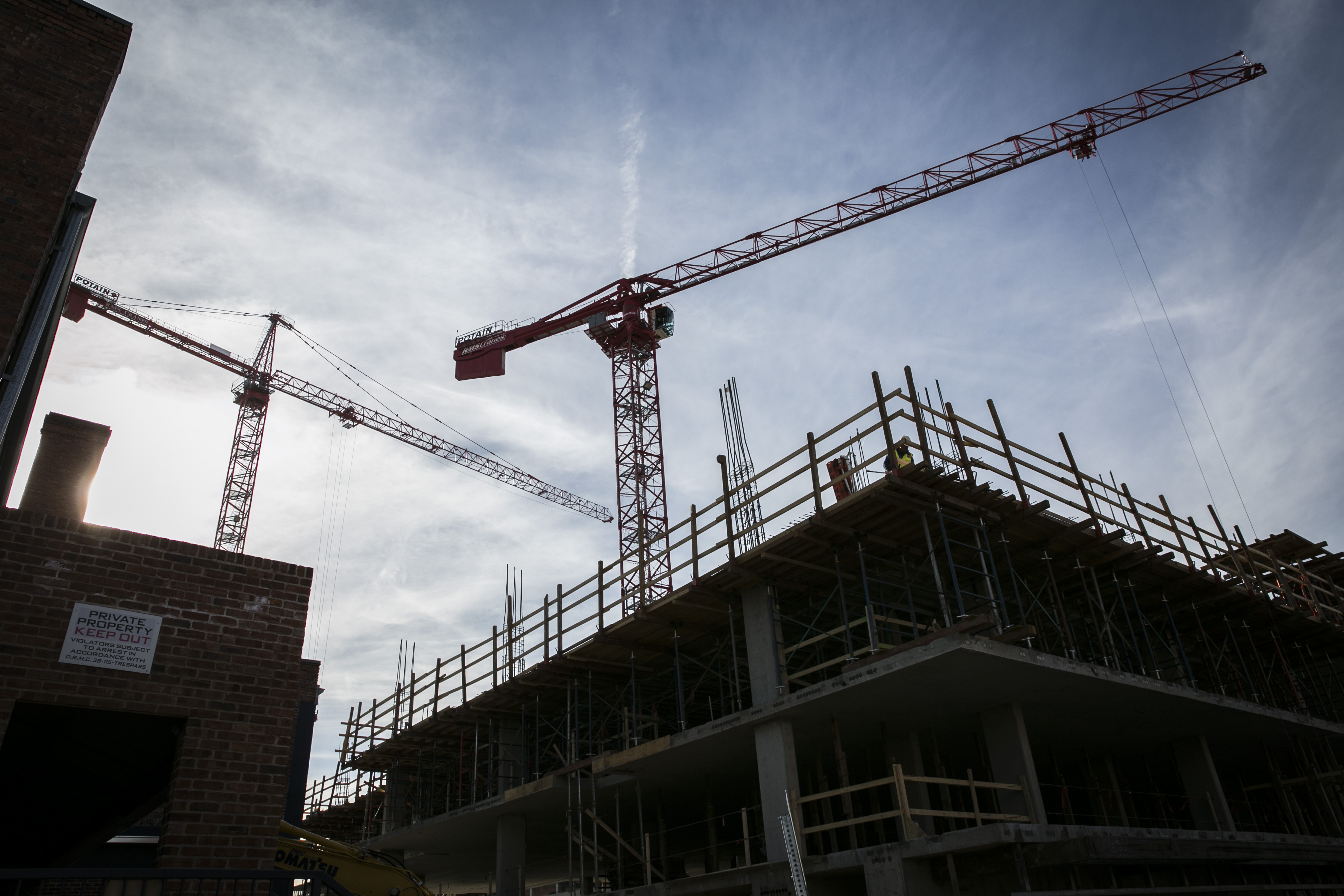 <p>Construction cranes stand over Wazee Street in downtown Denver on Thursday, Feb. 18, 2016. The site will house a 170-room hotel and six-story office project.</p>