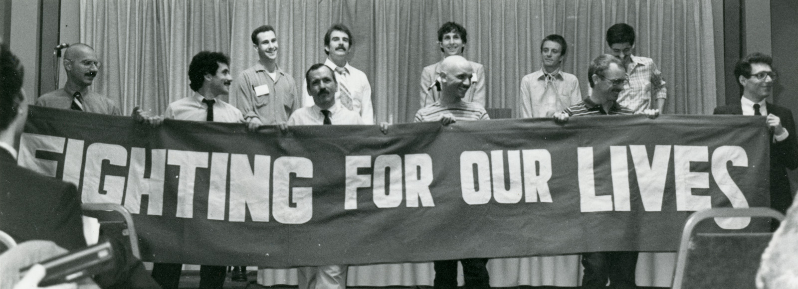 """<p>Richard Berkowitz(standing behind the Tin """"Fighting,"""" second from the left in the front row)and other AIDS activists unfurl a banner at a gay and lesbian health conference in Denver. Berkowitz is the only person pictured who is still alive.</p>"""