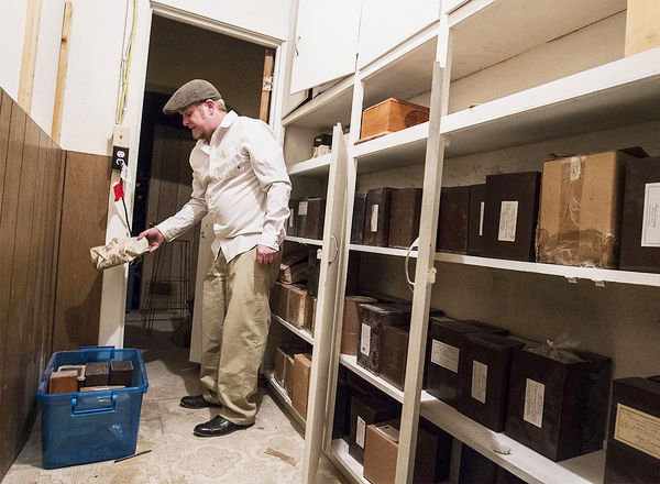 <p>Rose Memorial Parlour owner Matthew Boyle examines some of the 175 cremains left behind - some for as long as 69 years - by previous owners of the funeral home.</p>
