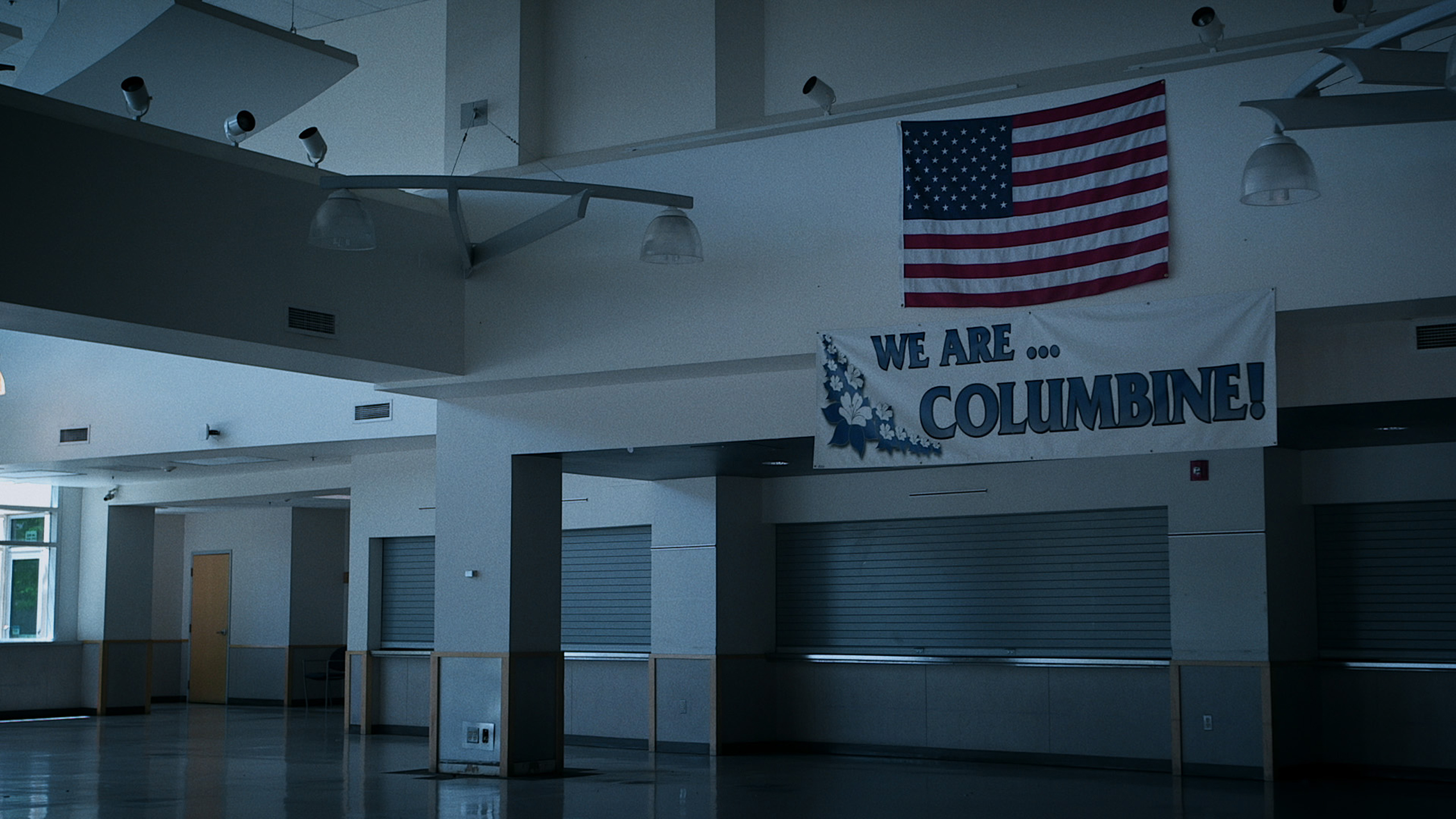 "<p>A ""We Are Columbine"" banner and American flag hang in the Columbine High School cafeteria.</p>"