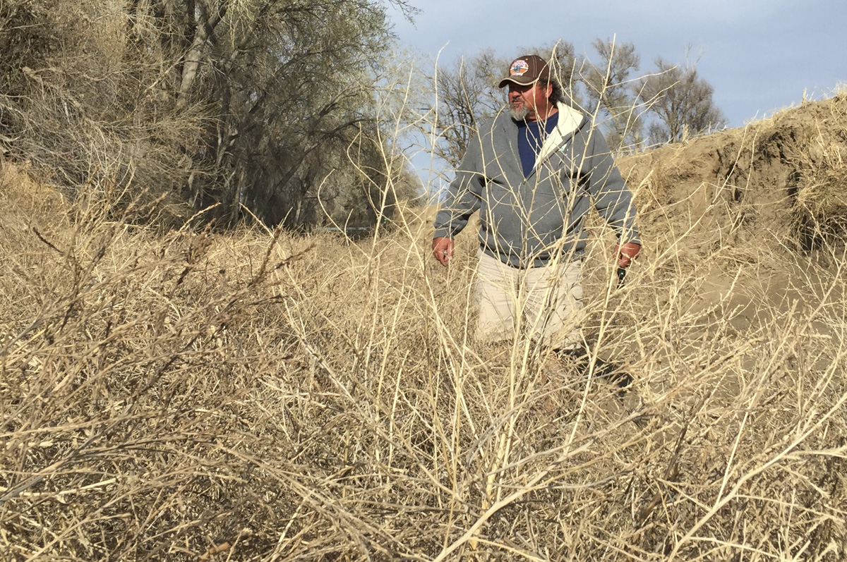 """<p>Dale Mauch stands in the dry ditch of the Fort Lyon Canal on Friday, April 10, 2015. The canalfeeds Arkansas River water onto his farm in southeast Colorado, but can quickly fill up with tumbleweeds. """"In 10 minutes, it can do this,"""" he said.</p><p></p>"""