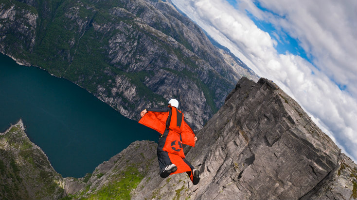 <p>A BASE jumper wearing a wingsuit flies off a cliff in Kjerag, Norway.</p>