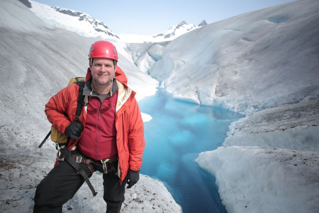 <p>Smithsonian natural history director Kirk Johnson surrounded by Alaskan ice.</p>