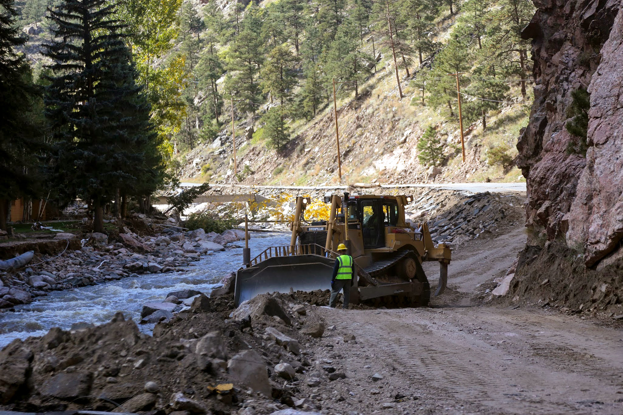 A construction worker guides a bulldozer working on US 34 between Estes Park and Drake, Colo., Oct. 3, 2013.