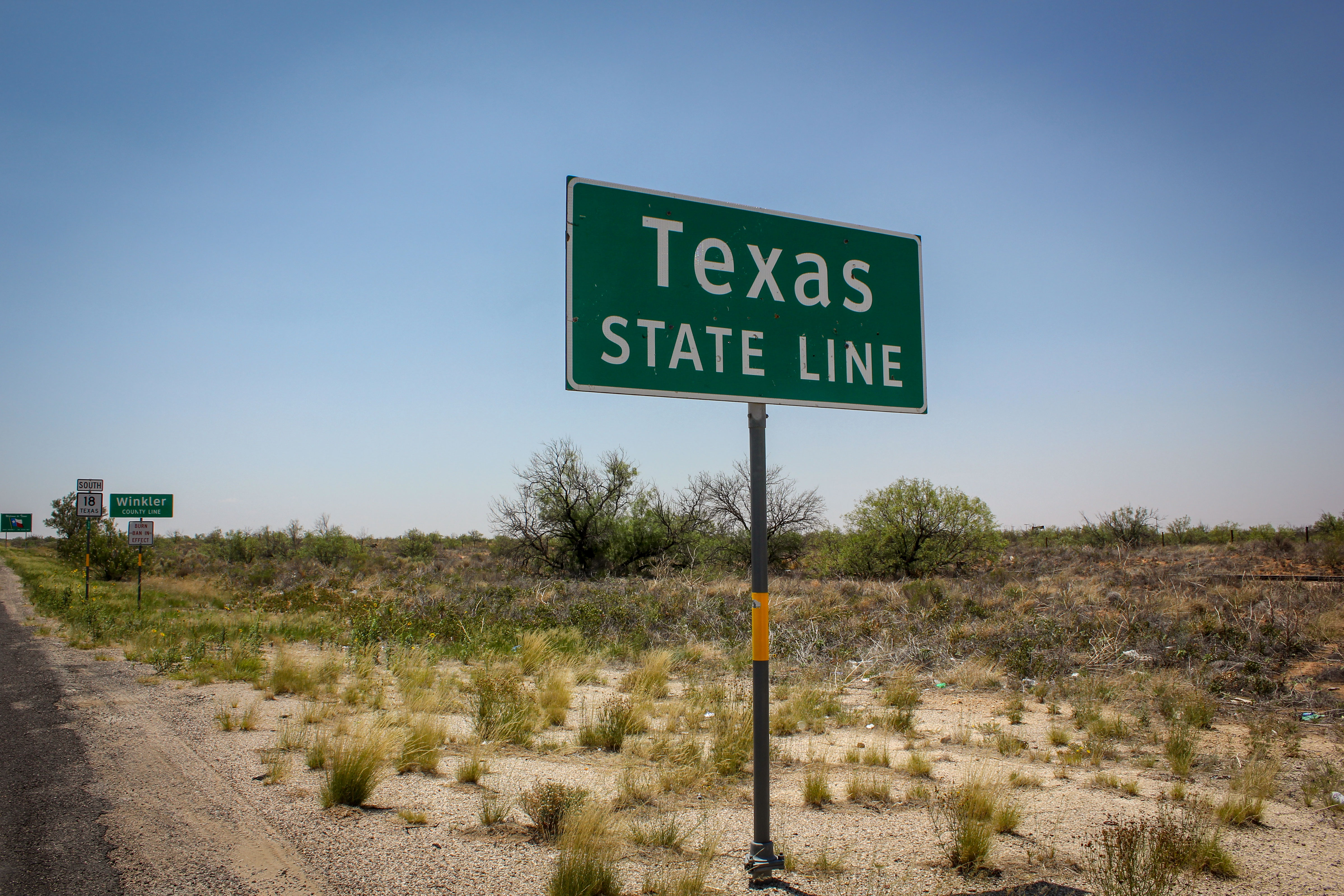 <p>A sign marks the Texas state line along the border of New Mexico.</p>