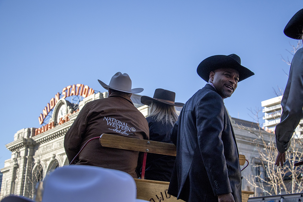 <p>Mayor Michael Hancock rides on a wagon as it passes Union Station in downtown Denver during the Stock Show Parade, Jan. 4, 2018.</p>