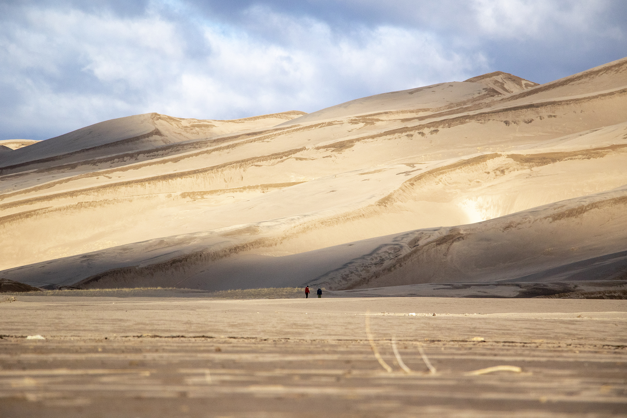A couple of people walk at the Great Sand Dunes National Park on April 13, 2019, during a student robotics challenge.
