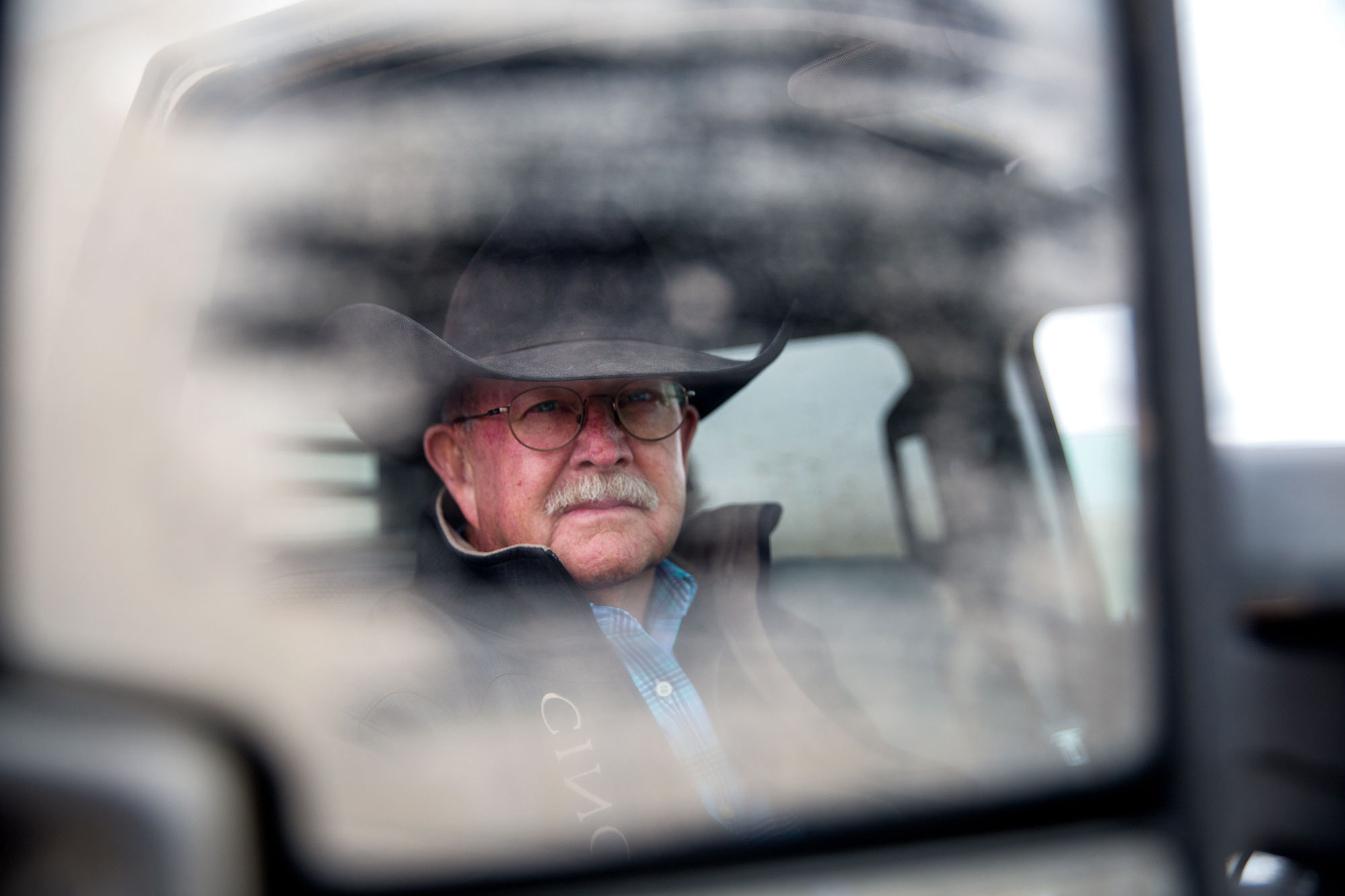 <p>Rancher and farmer Terry Swanson seen in the muddy rearview mirrorin his pickup truck as he showsjournalists around his land in Baca County on May 20, 2019.</p>