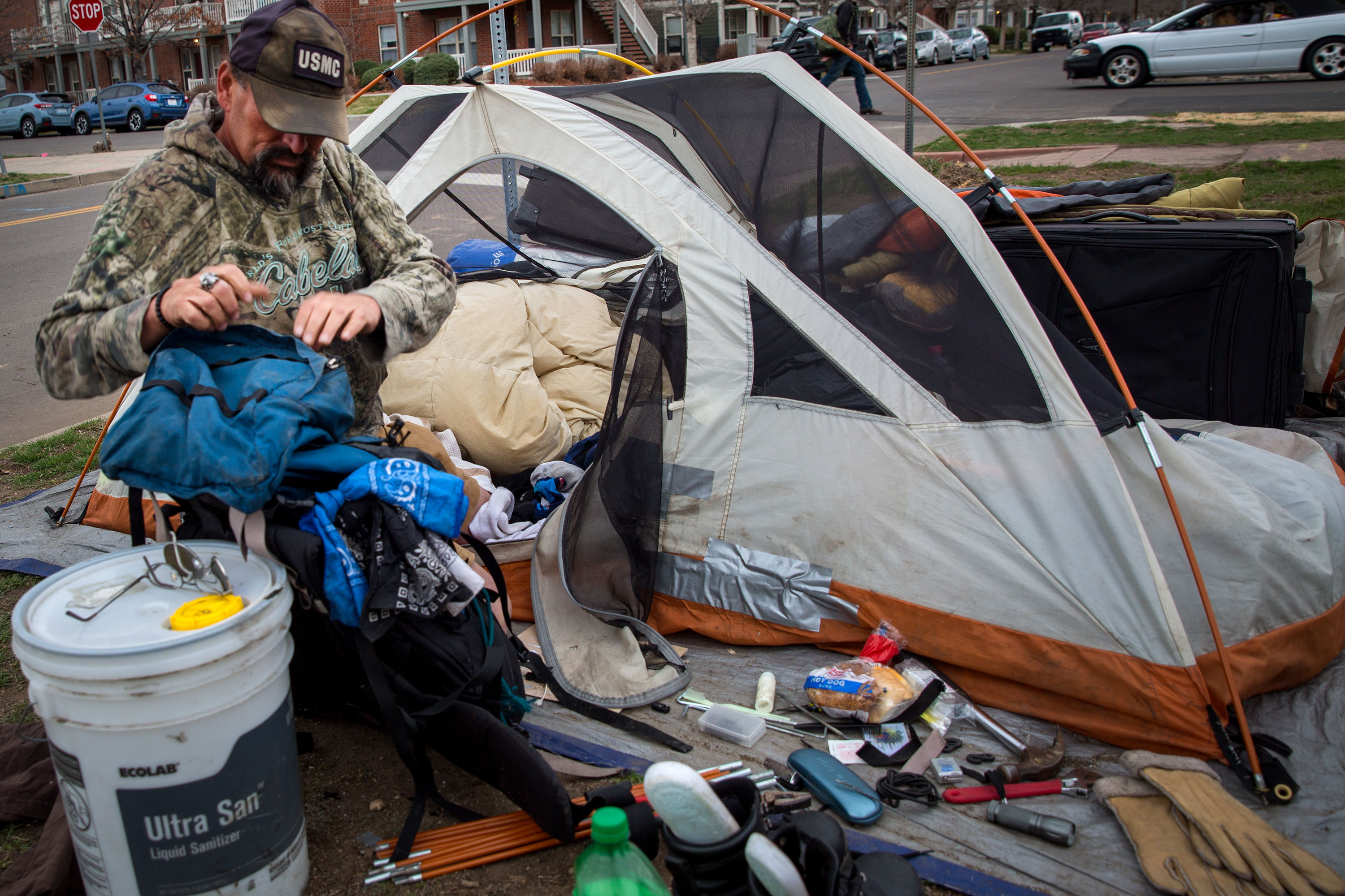 "<p>After putting his tent up for the evening on Denver's Arapahoe Street near 27th Avenue, ""Wolf"" starts picking up and packing away his belongings  on March 27, 2019. The camp where he lives asks everyone there to keep their sites tidy, and they watch out for each others belongings during the day. </p>"