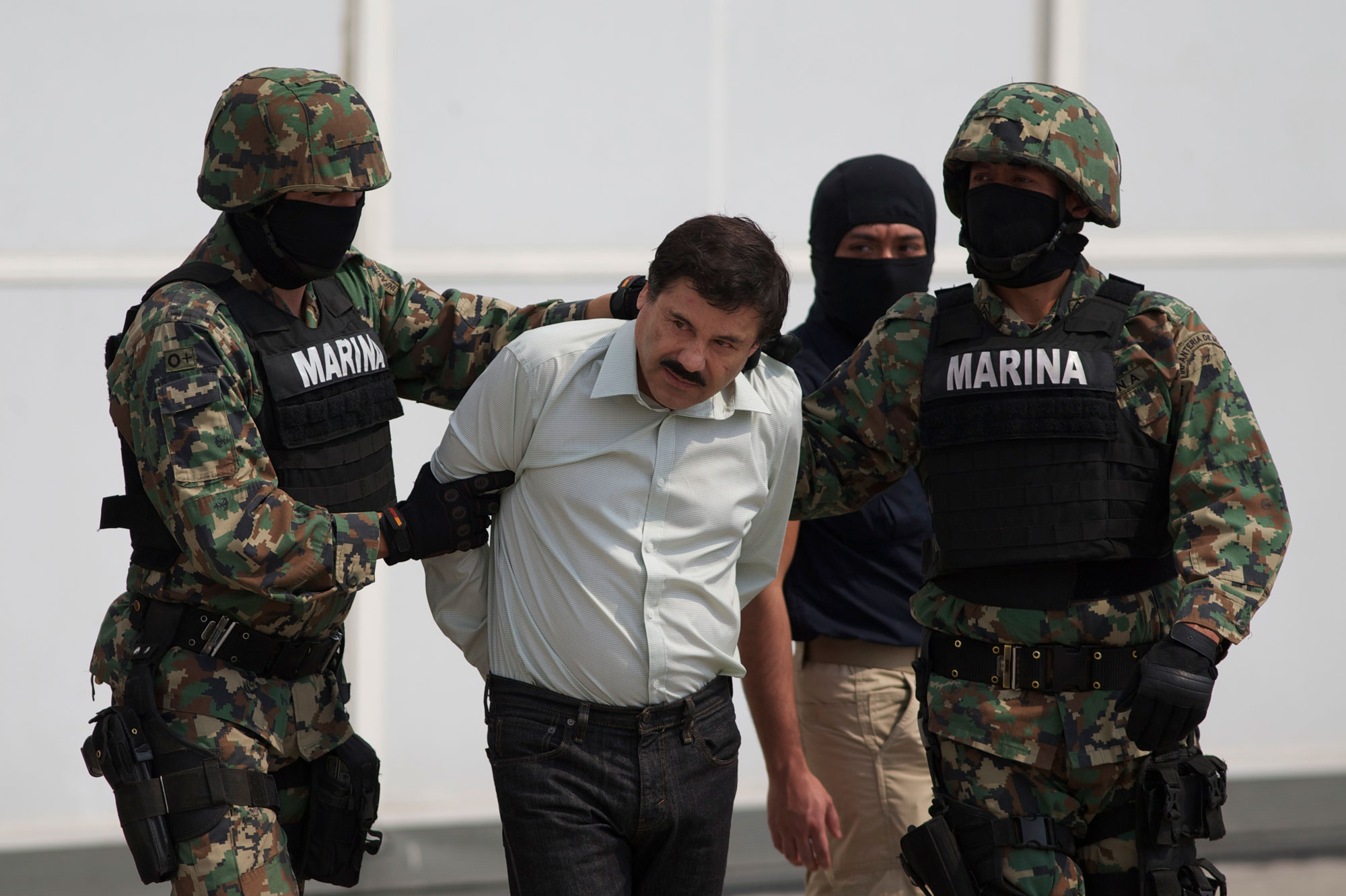 "<p>In this Saturday, Feb. 22, 2014 file photo, Joaquin ""El Chapo"" Guzman, center, is escorted to a helicopter in handcuffs by Mexican navy marines at a hanger in Mexico City, after he was captured overnight in the beach resort town of Mazatlan.</p>"