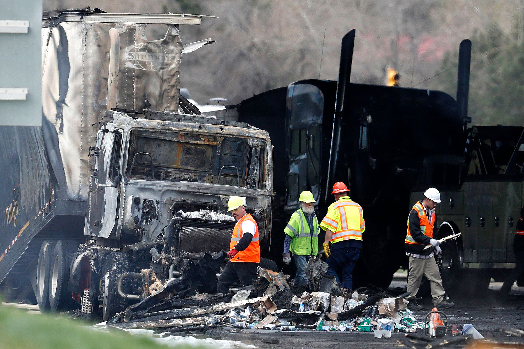 "Workers clear debris from the eastbound lanes of Interstate 70 on Friday, April 26, 2019, in Lakewood, Colo., a deadly pileup involving semi-truck hauling lumber on Thursday. Lakewood police spokesman John Romero described it as a chain reaction of crashes and explosions from ruptured gas tanks. ""It was crash, crash, crash and explosion, explosion, explosion,"" he said."