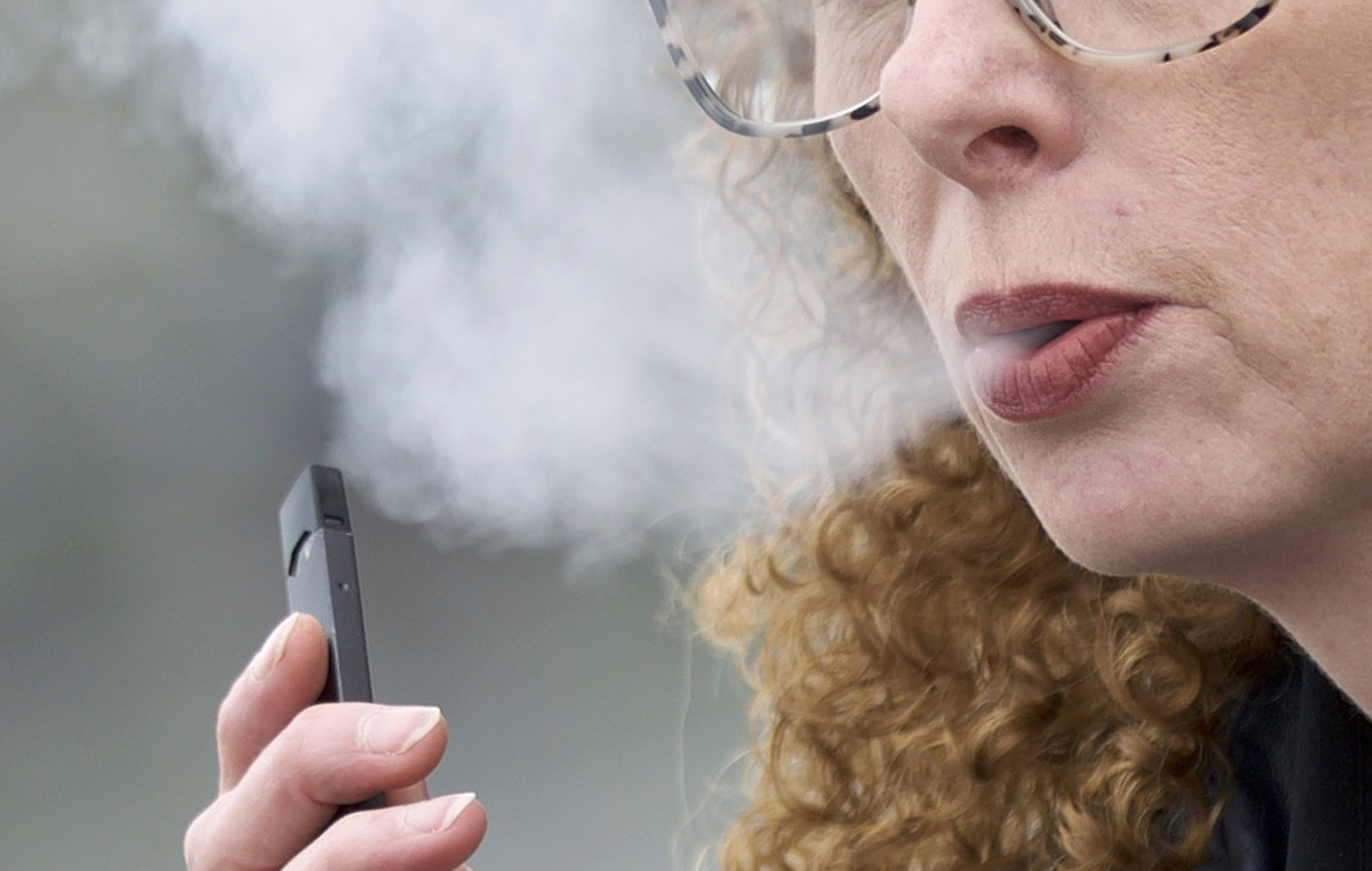 In this April 16, 2019 file photo, a woman exhales while vaping from a Juul pen e-cigarette in Vancouver, Wash. Using e-cigarettes, often called vaping, has now overtaken smoking traditional cigarettes in popularity among high school students, says the Centers for Disease Control and Prevention.