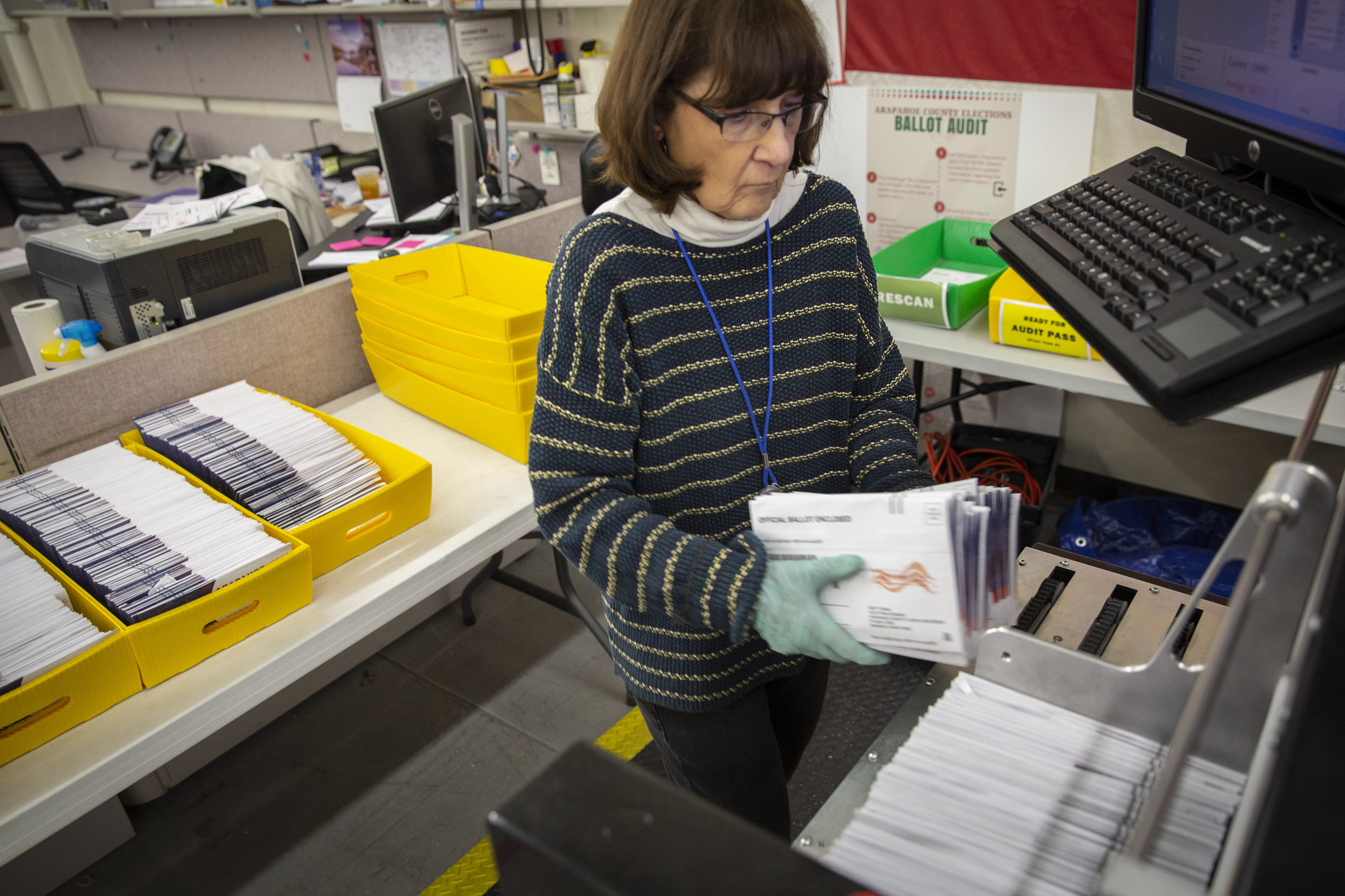 Marleen Cohen of Aurora loads ballots into a sorting machine atthe Arapahoe County Elections Facility in Littleton, Colorado, Tuesday, Oct. 30, 2018.
