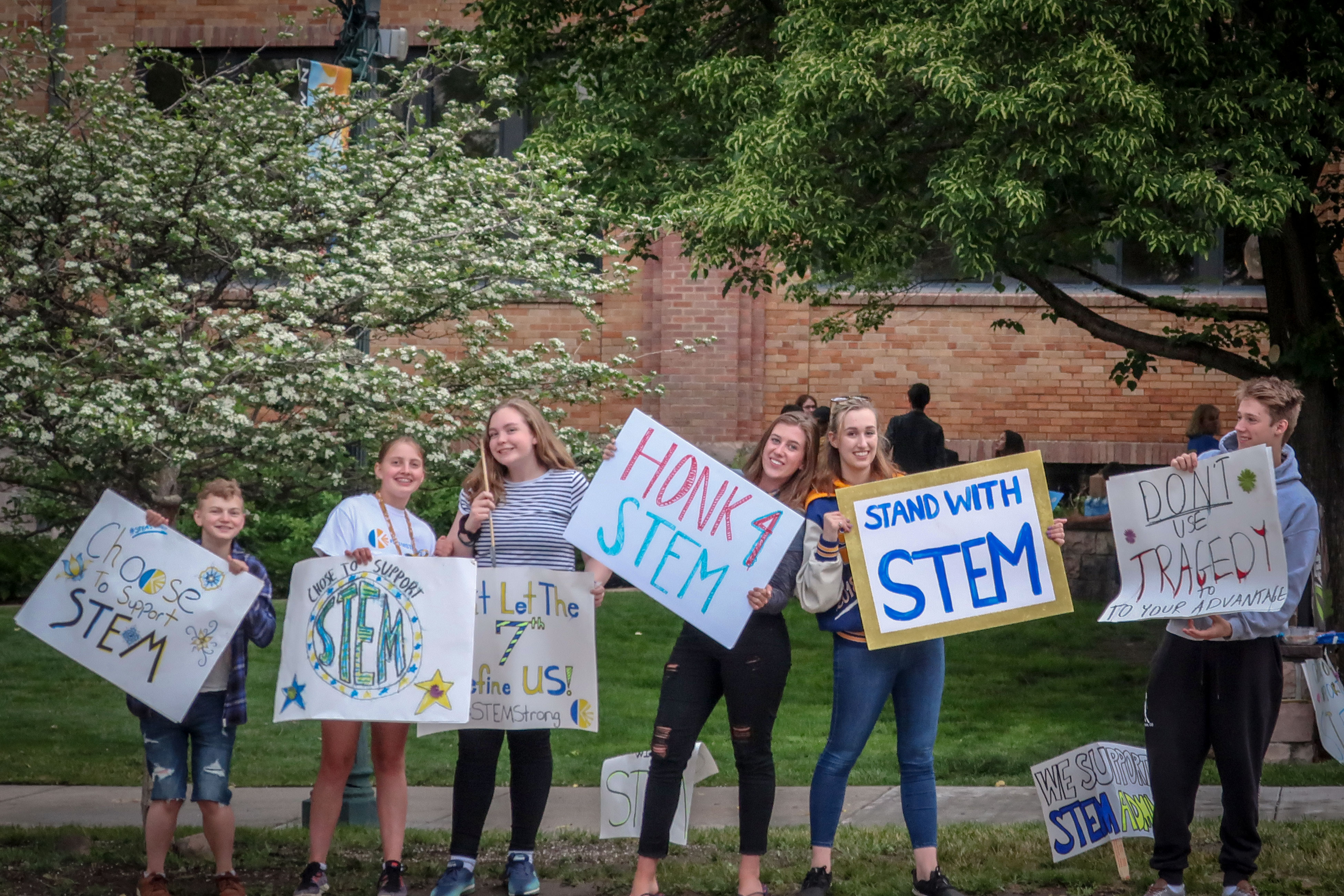 <p>STEM students waive signs outside the Douglas County School Adminstration building in Castle Rock, June 18, 2019.</p>