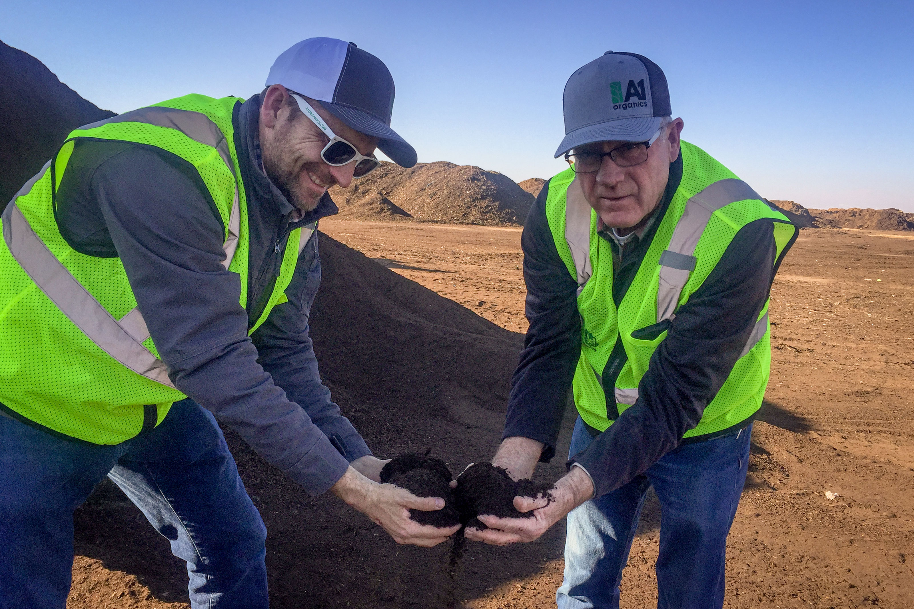 """<p>A1 Organics Vice President Bob Yost (right) and<span style=""""color: rgb(64, 69, 64);"""">Marketing Manager</span> ClintonSander (left) pose with some fresh compost at A1'sKeenesburgcomposting facility. The Denver City Council is working with A1 to extend the benefits of the city's compost pickup program.</p>"""