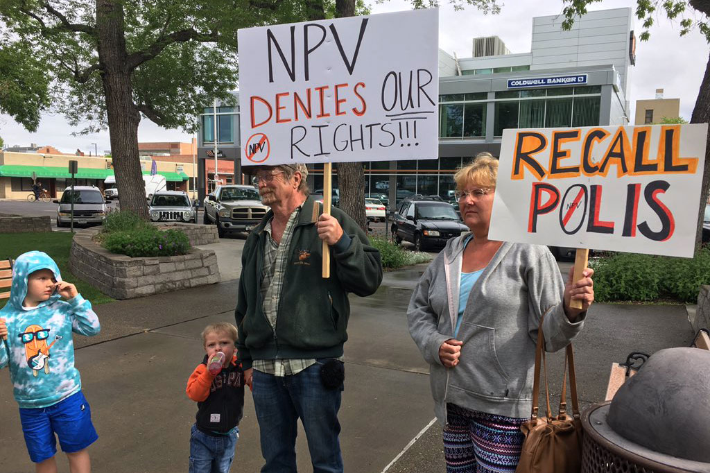 <p>A family with homemade signs arrives at a Republican rally in Grand Junction on Friday, May 10, protesting new Democratic legislation.</p>