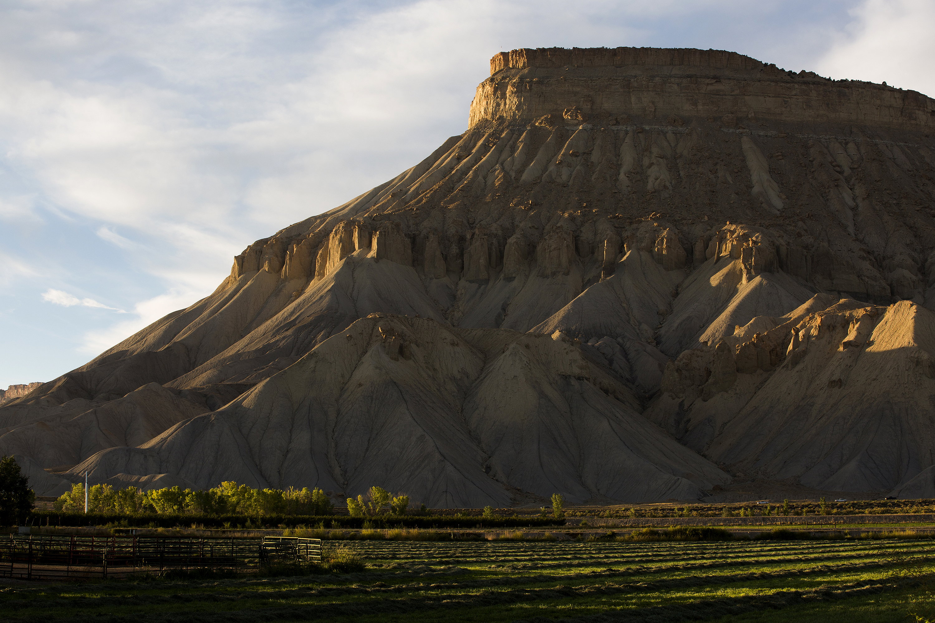 The arid Book Cliffs dominate the view from Palisade and Grand Junction. The highest point on the iconic geologic formation is Mt. Garfield. This photo was made in October looking across freshly cut hayfields from G Road.