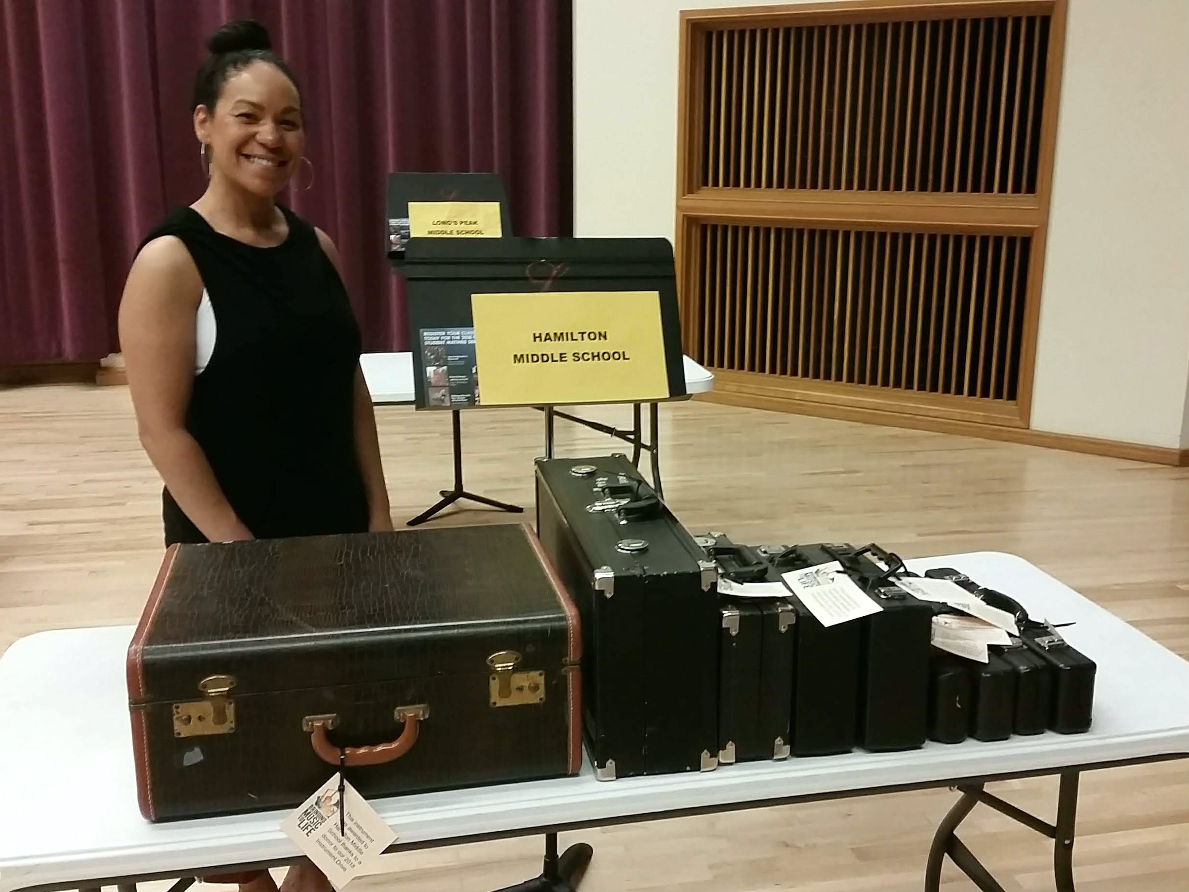 <p>Hamilton Middle School band teacher Priscilla Shaw poses with instruments she's picking up from the Bringing Music to Life instrument distribution day.</p>