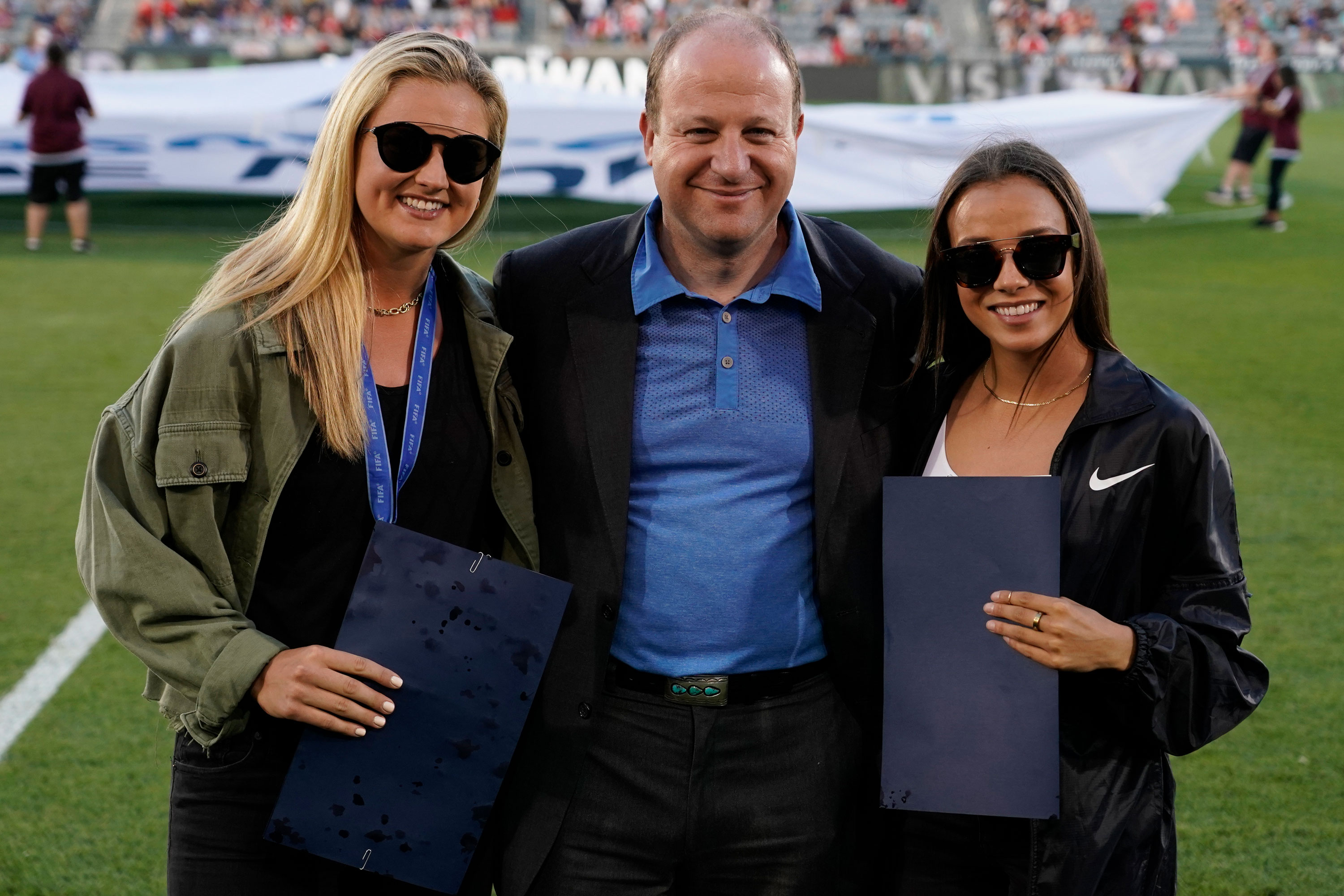 Colorado Gov. Jared Polis, center, poses with U.S. Women's National team players Lindsey Horan, left, and Mallory Pugh, right, during halftime at an international friendly soccer match between the Colorado Rapids and Arsenal FC, Monday, July 15, 2019, in Commerce City, Colo.