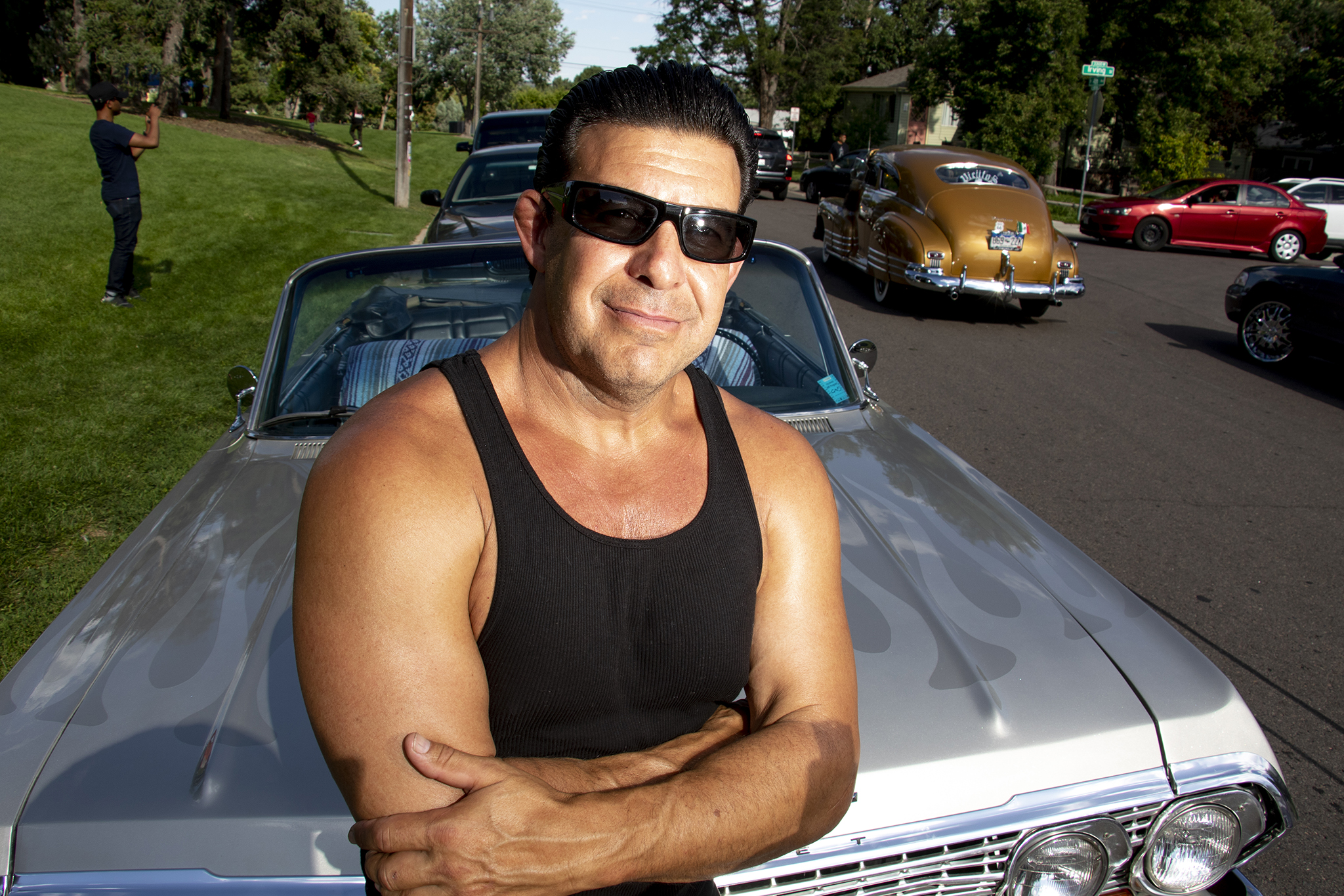 Officer Mark Garcia poses for a portrait with his low rifer at Barnum Park after a cruise down Federal Boulevard. Aug. 25, 2019.