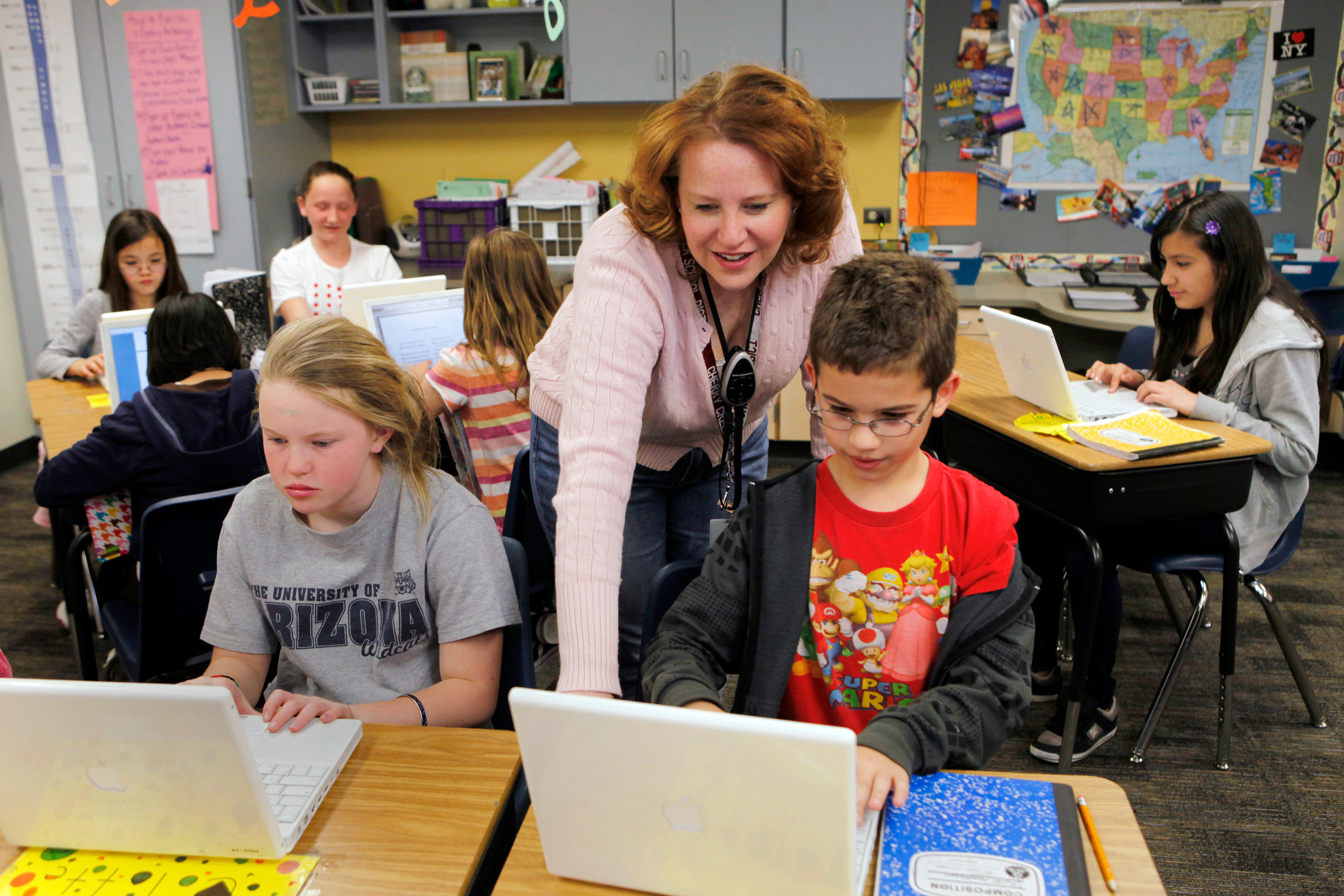 In this April 22, 2011 photo, High Plains Elementary School teacher Jennifer Williford, center, works with Colette Jackson, 11, and Skyler Matteson, 10, right, on a computer project in her fifth grade class at the school in Englewood, Colo.