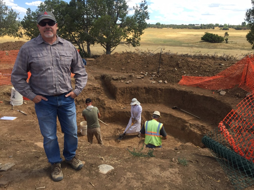 Archaeologist, Rand Greubel, standing in front of the last active dig site of the project