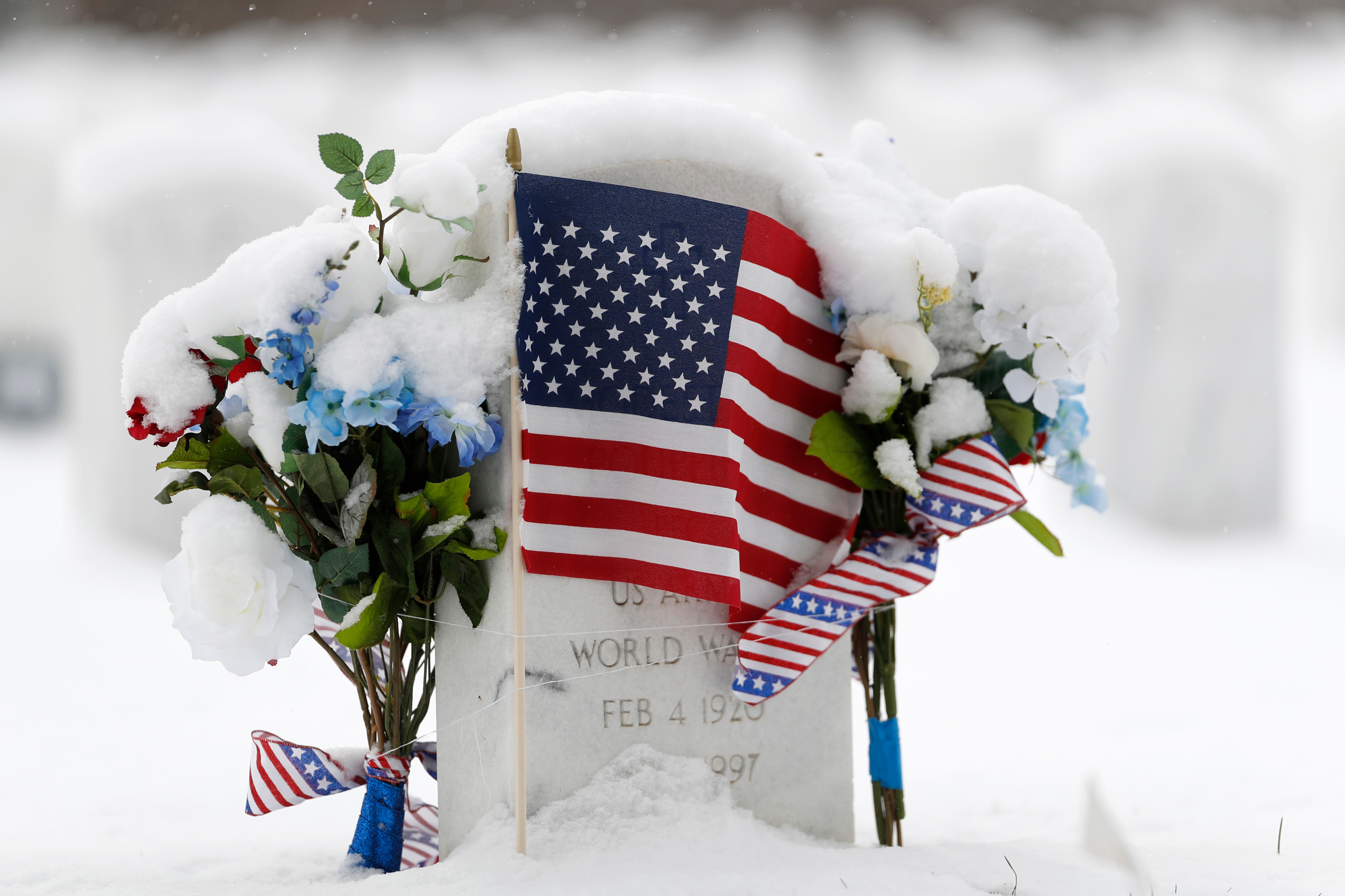As a light snow falls, a United States flag marks the grave of World War II veteran Modestee Pouppirt in Fort Logan National Cemetery, Sunday, Nov. 11, 2018, in Sheridan, Colo.