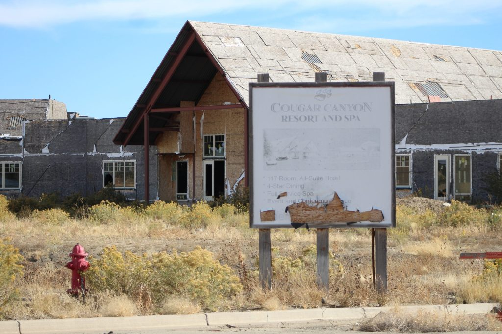 "A faded sign at what was to be the Cougar Canyon resort spa. Construction was abruptly halted nearly a decade ago. The sign says, ""117-room all suite hotel, four-star dining, full-service spa, event and conference space. Four-star hotel."""