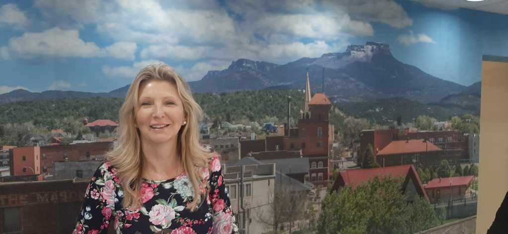 Cy Michaels heads up the City of Trinidad's Tourism Board and is co-owner of La Quinta Inn and Suites. She's standing in front of a photograph of Fisher's Peak as seen from downtown Trinidad.