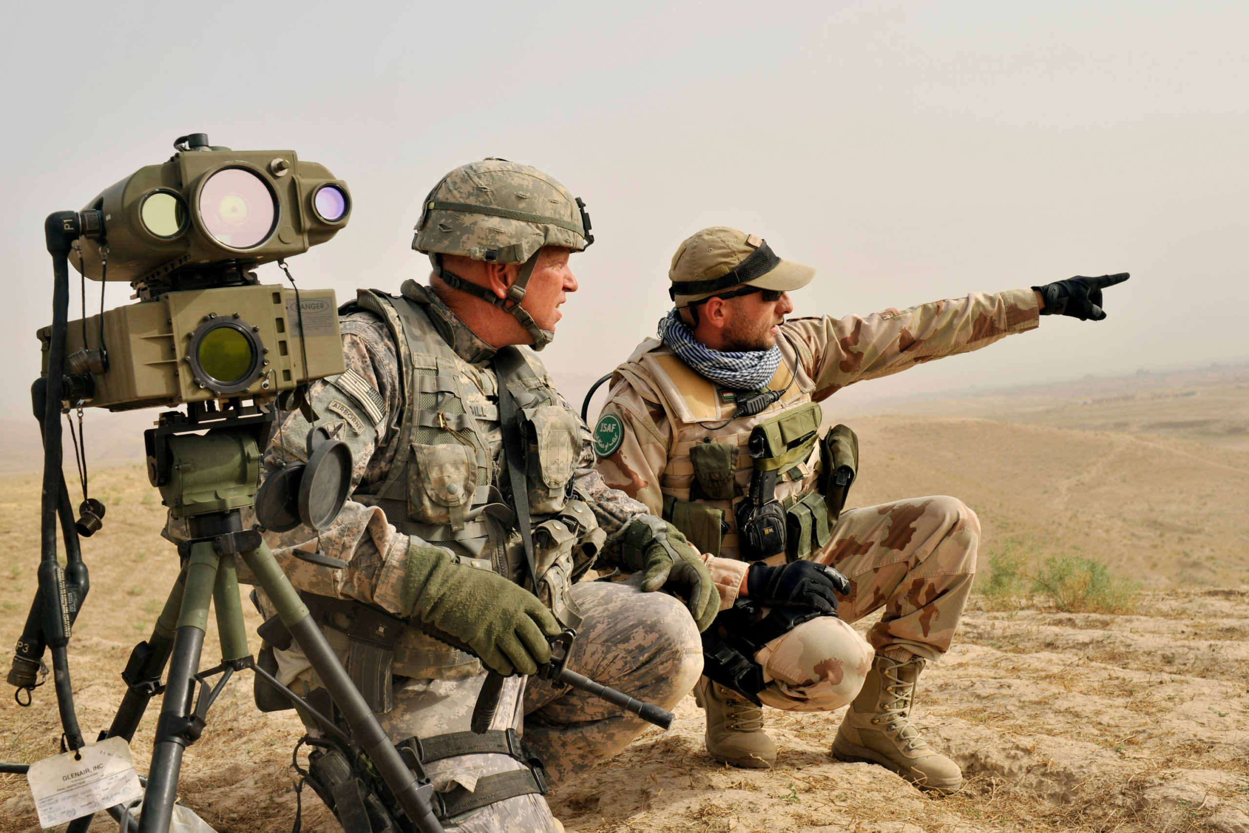 1st Sgt David Gill from Alliance, Oh of the OMLT Team Orthos from 1-145AR RGT, left, and Hungarian military adviser SFC Otto Szatmari, right, look at a hill while searching for pro-Taliban fighters near Kuk Cenar, Baghlan province of northern Afghanistan, Wednesday, July 8, 2009.
