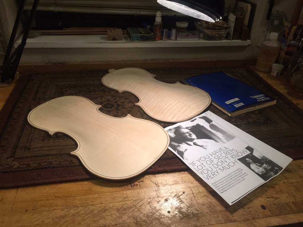 Front and back panels for the viola Mijares is building lie alongside an article about his mentor and Violin School of America founder, Peter Prier.