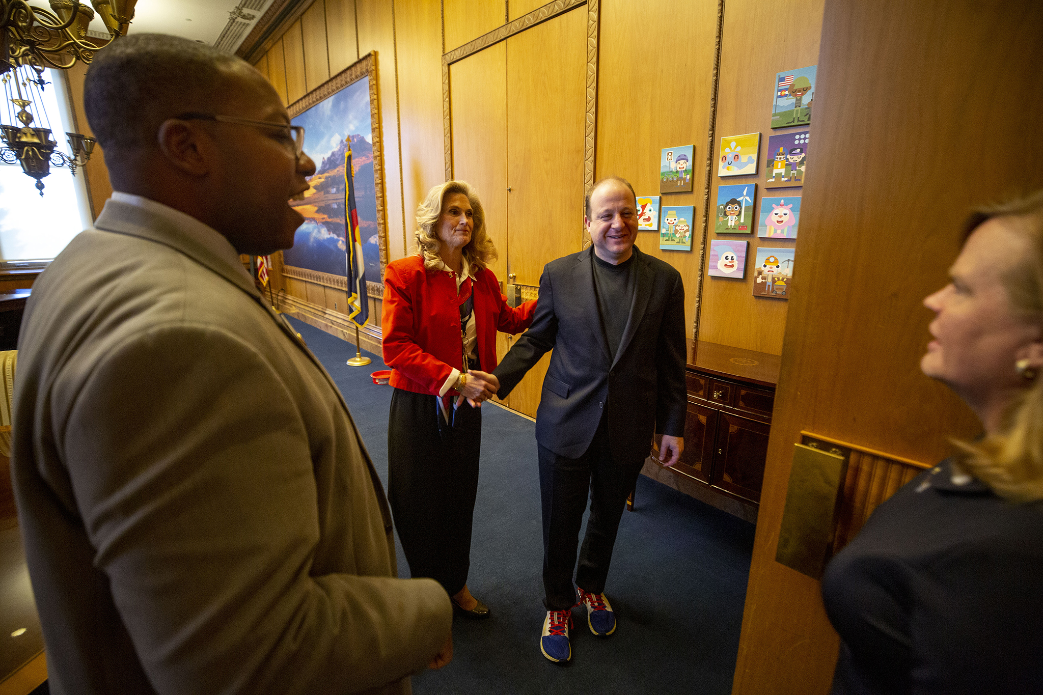 State Reps. Jovan Melton (left to right), Perry Buck and Meg Froelich inform Gov. Jared Polis that the House is ready for business on The first day of the 2020 legislative session. The Colorado State Capitol. Jan. 8, 2020.