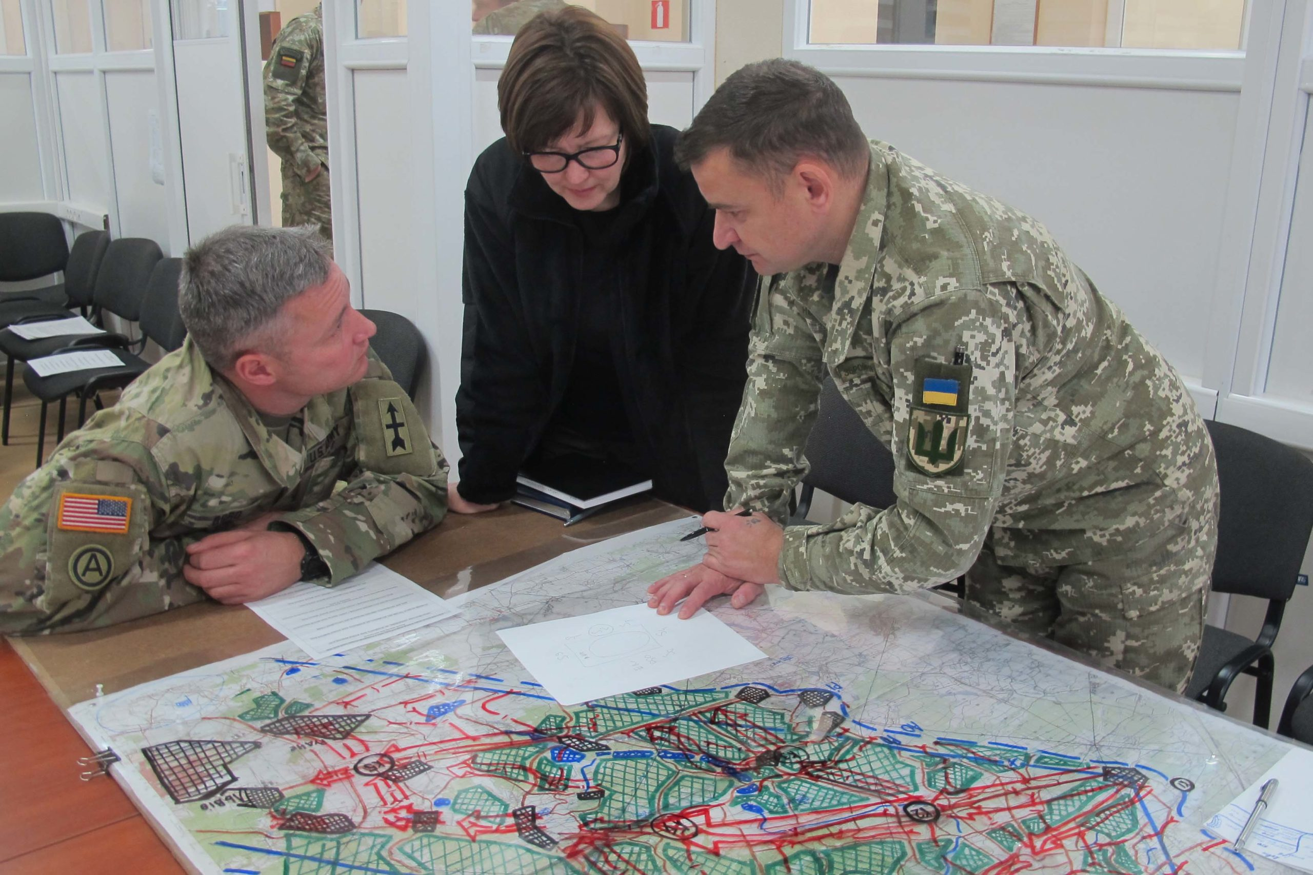 A Ukrainian and American soldier talk through a potential battlefield scenario with the help of an interpreter at the Combat Training Center in Yavoriv, Ukraine. The Wisconsin National Guard is helping train Ukraine's military.