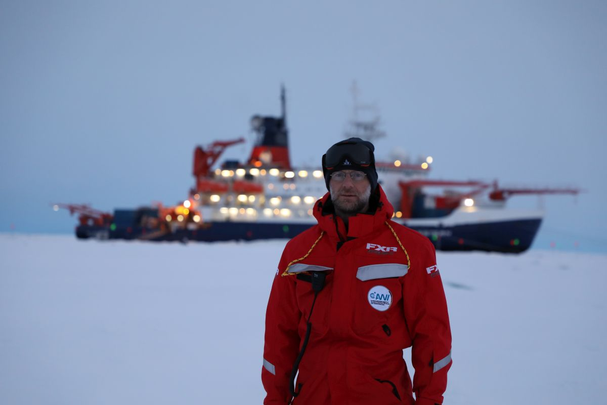 University of Colorado scientist Matthew Shupe in 2019 stands in front Polarstern during the MOSAiC mission. The ship is moored to an ice floe drifting through the Arctic Ocean.