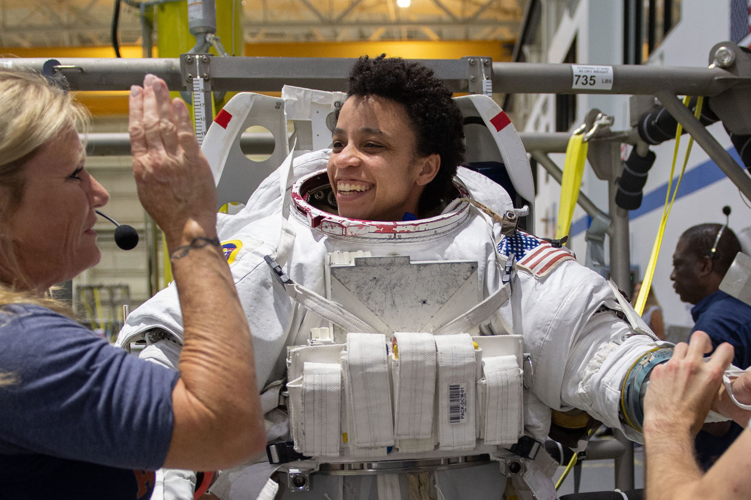 Then-astronaut candidate Jessica Watkins is helped into a spacesuit prior to underwater spacewalk training at NASA Johnson Space Center's Neutral Buoyancy Laboratory in Houston, May 22, 2019.