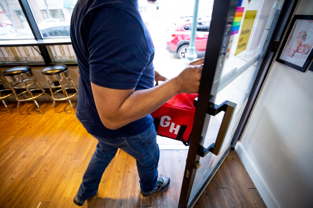 Rai gingerly opens the door after grabbing an order from Ice Cream Riot. He has a bottle of hand sanitizer waiting for him back in the car.
