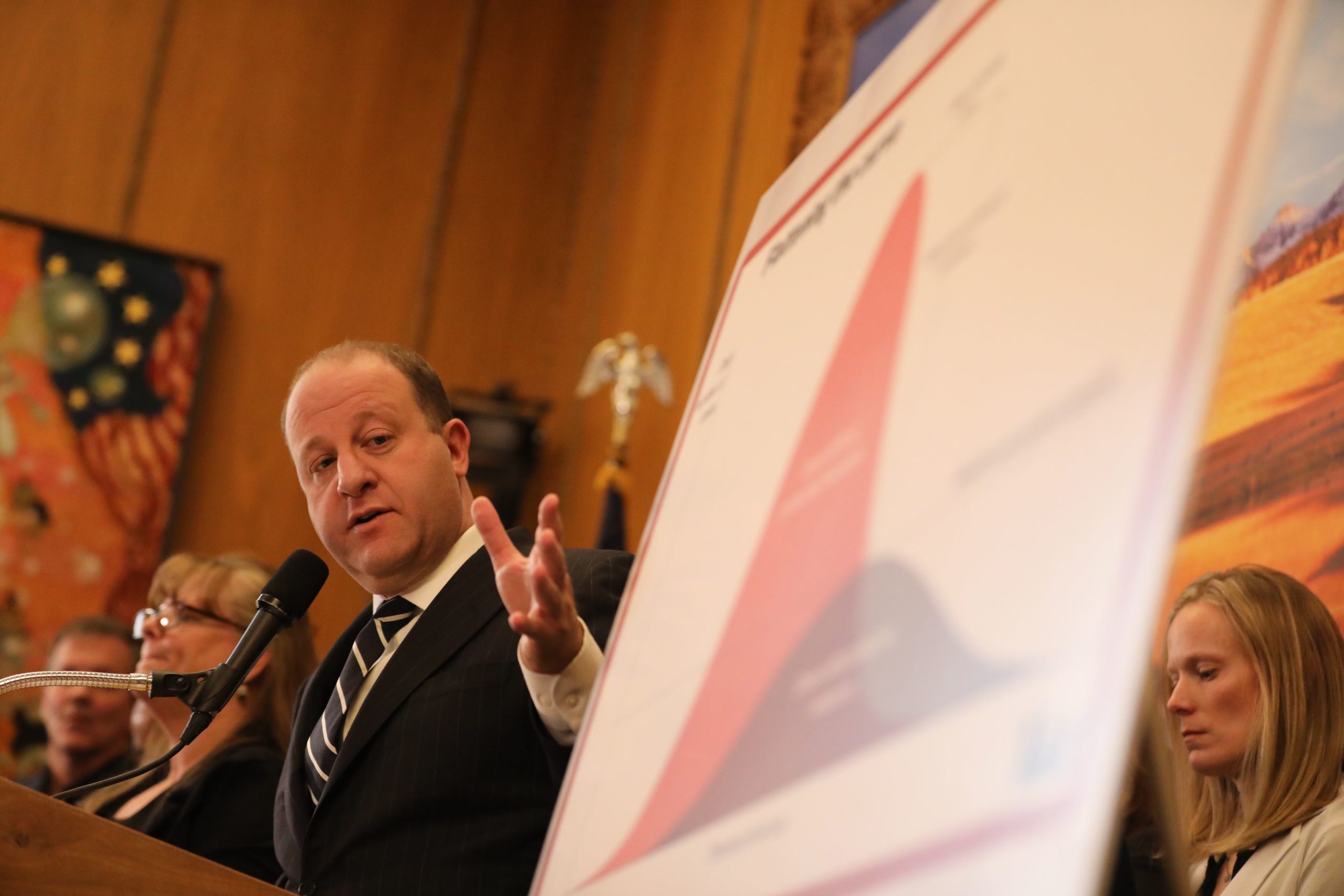 """Gov. Jared Polis provides an update on coronavirus in Colorado on Friday, March 13. Next to him is a version of the popular """"flatten the curve"""" chart about slowing the spread of an epidemic."""