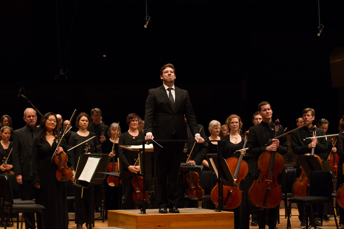 Brett Michell, conductor of the Colorado Symphony stands facing the audience with the symphony after a performance.