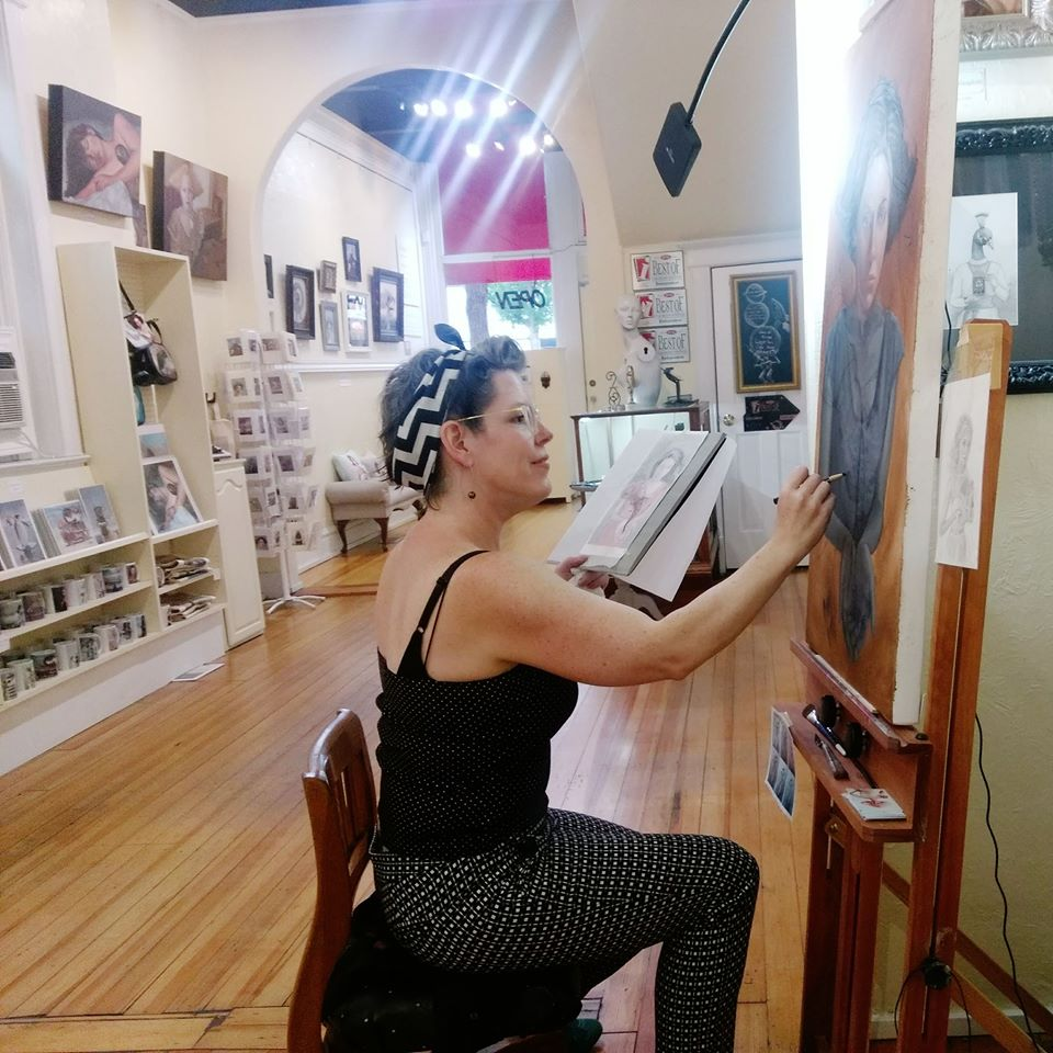 A picture of Lisa Chavez painting in her gallery.